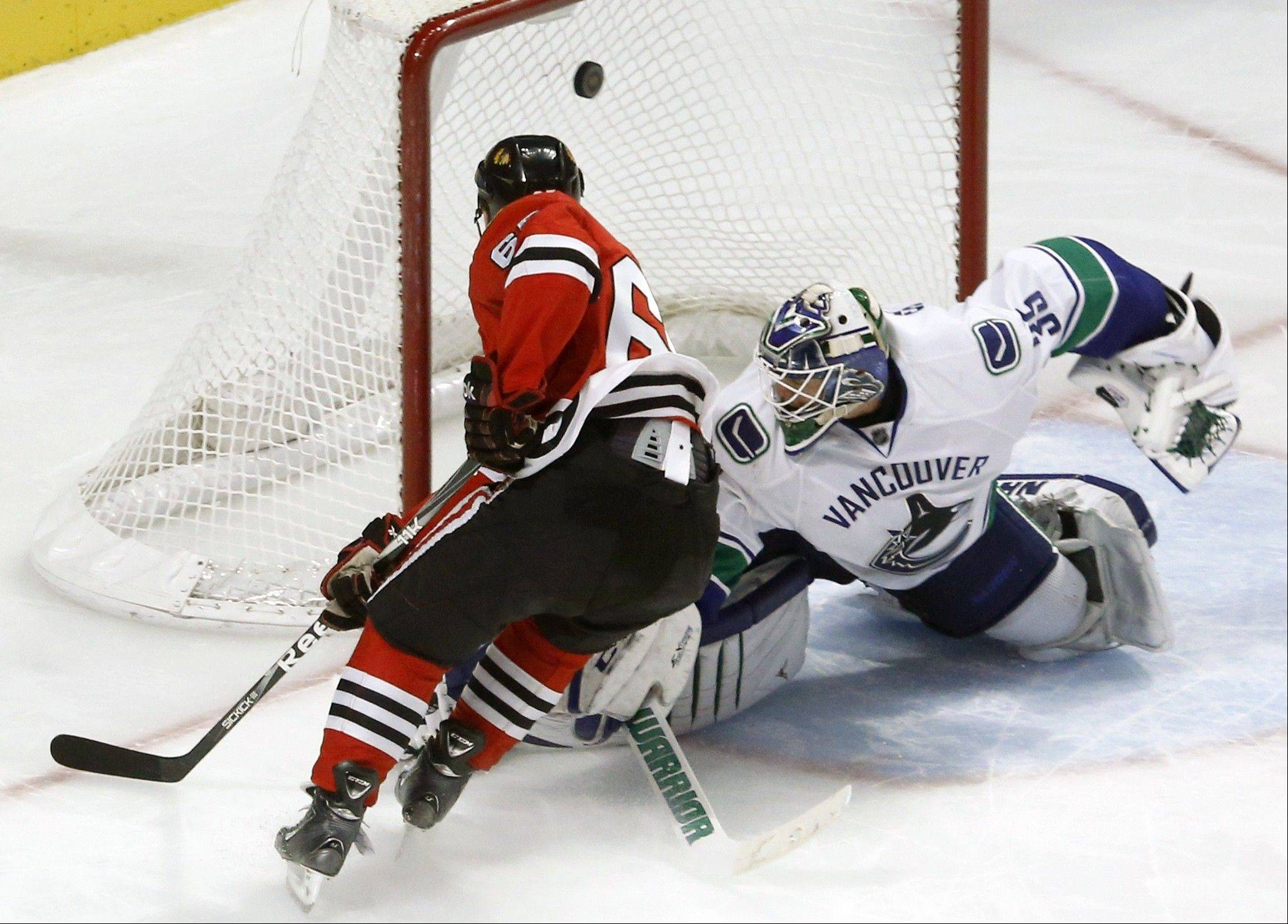 Chicago Blackhawks center Andrew Shaw scores against Vancouver Canucks goalie Cory Schneider during the shootout.