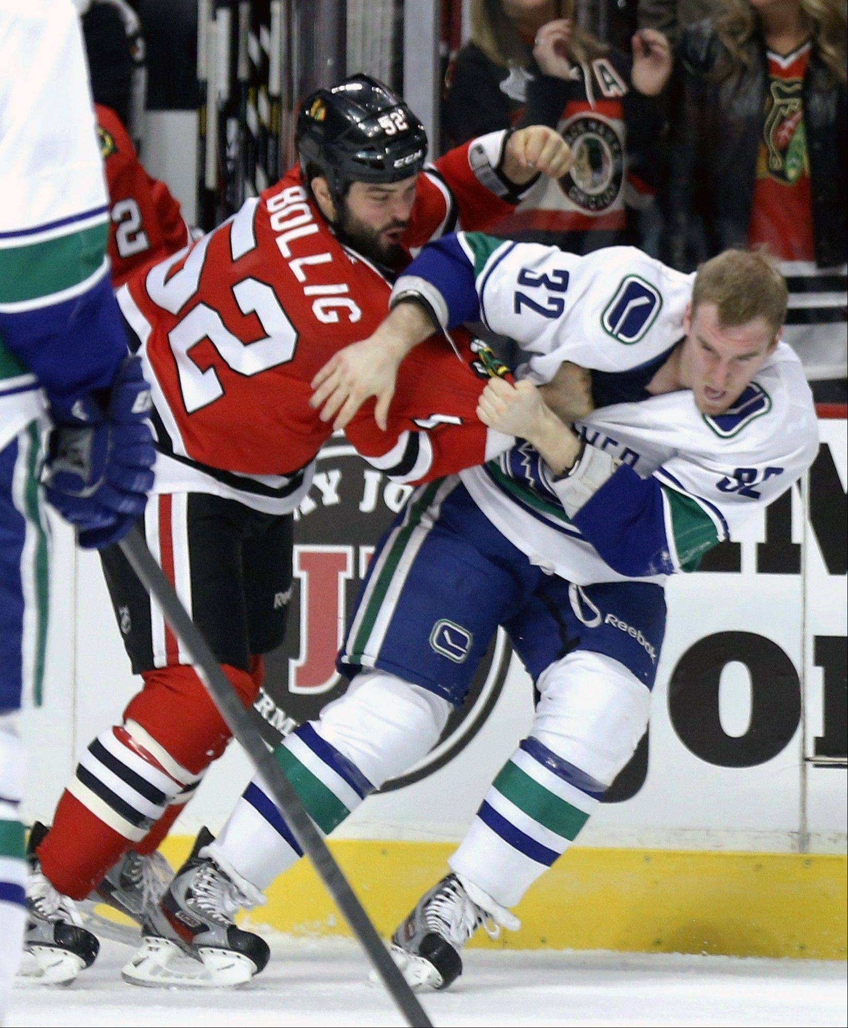 Chicago Blackhawks left wing Brandon Bollig fights Vancouver Canucks right wing Dale Weise during the first period.