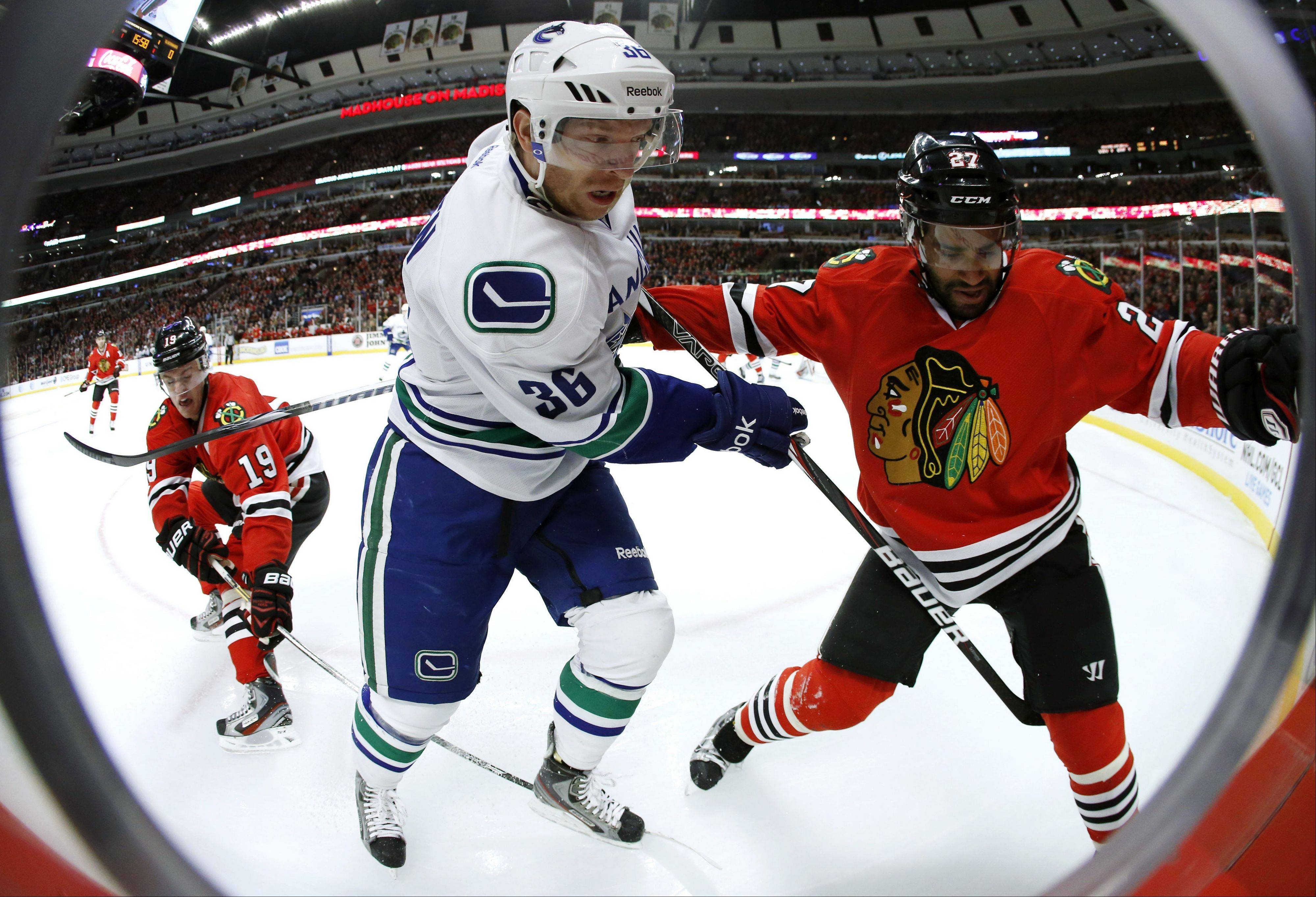 In this photo made using a fisheye lens, Vancouver Canucks right wing Jannik Hansen battles Chicago Blackhawks defenseman Johnny Oduya for a loose puck as Chicago Blackhawks' Jonathan Toews enters the play during the first period.