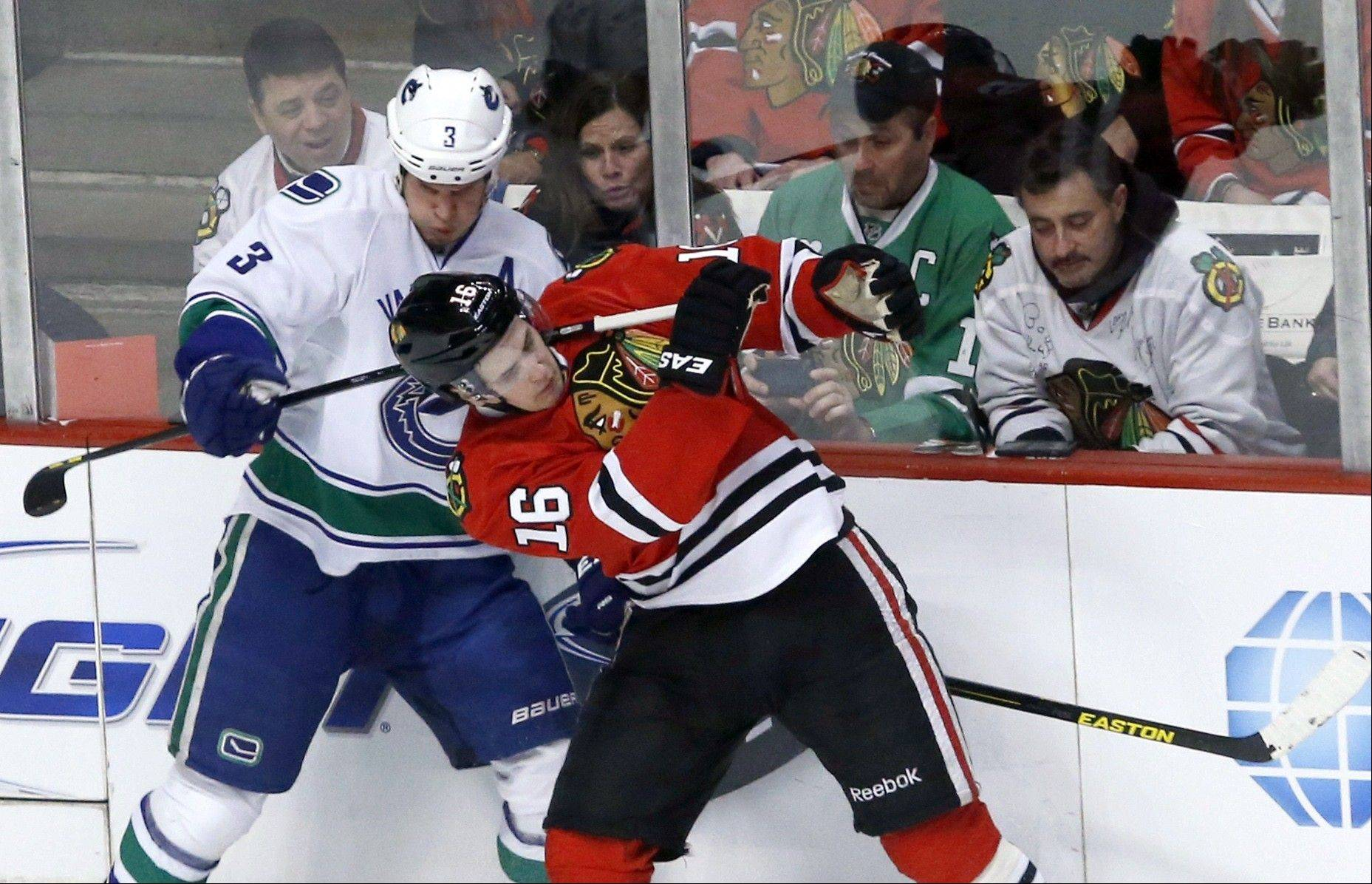 Vancouver Canucks defenseman Kevin Bieksa pulls back on the stick of Chicago Blackhawks center Marcus Kruger during the second period.