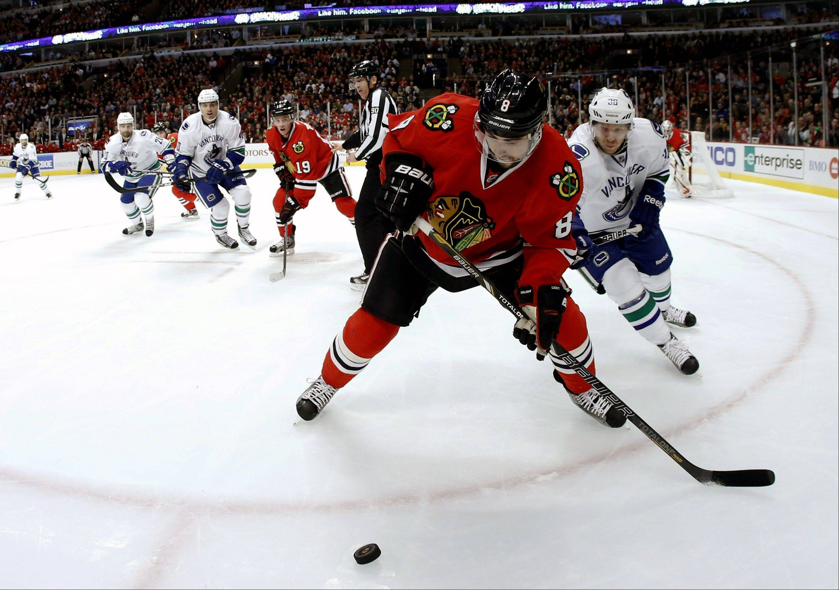 Chicago Blackhawks defenseman Nick Leddy tries to clear the puck under pressure from Vancouver Canucks right wing Jannik Hansen in the first period.