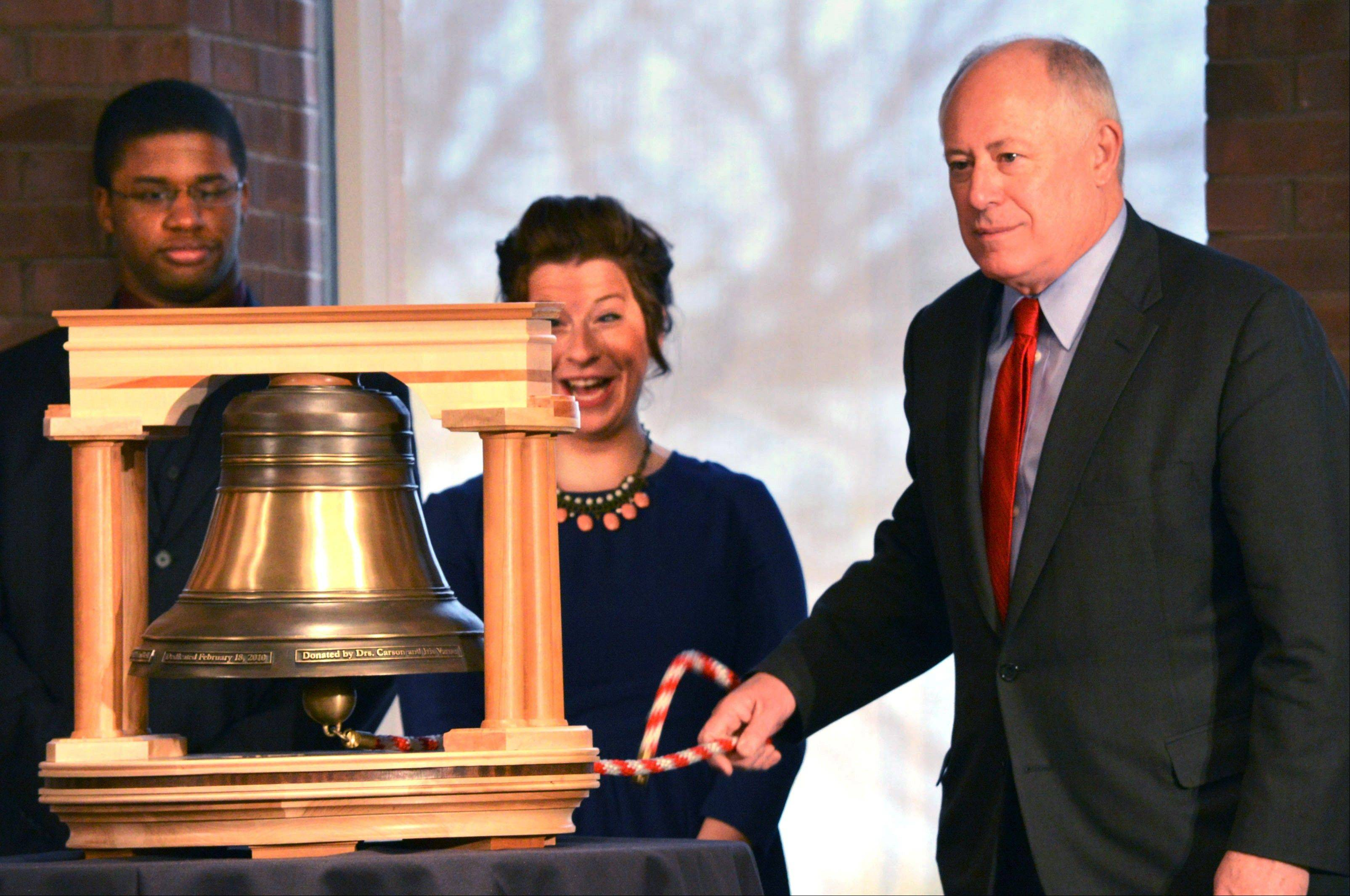 Gov. Pat Quinn rings the replica Old Main Bell at Illinois State University in Normal on Thursday after announcing a $54 million capital investment to build a new fine arts complex on the campus. Reacting during Founders Day 2013 are ISU seniors Abby Vombrack, center, a theater education major from Buffalo Grove, and Austin Robbins, an arts technology and fine arts major from Bolingbrook,