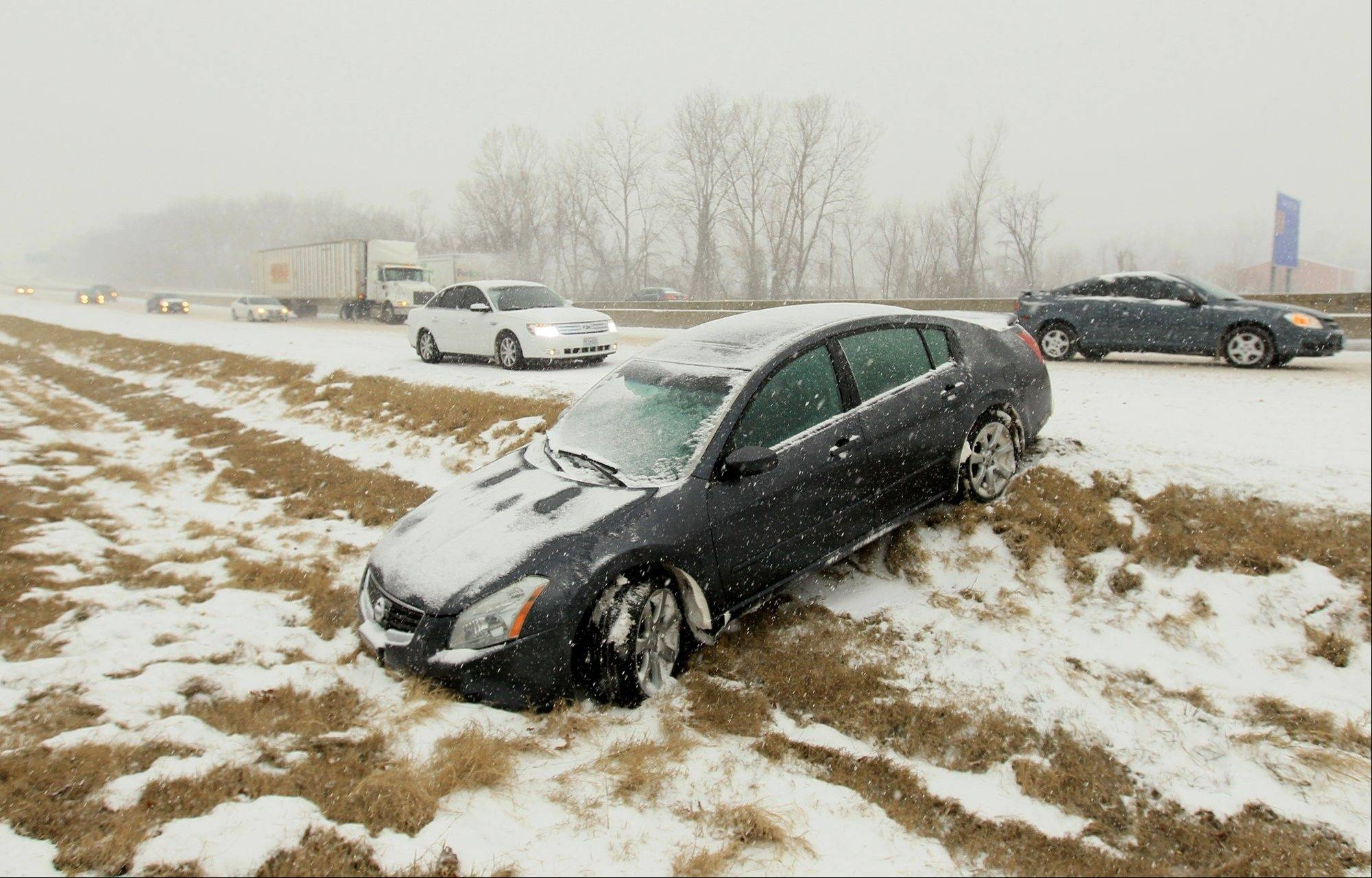 A car is stuck in a ditch after spuning out on Interstate 70 East near Lake Saint Louis, Mo., on Thursday. Blinding snow, at times accompanied by thunder and lightning, bombarded much of the nation�s midsection Thursday, causing whiteout conditions, making major roadways all but impassable and shutting down schools and state legislatures. Freezing rain and sleet were forecast for southern Missouri, southern Illinois and Arkansas.