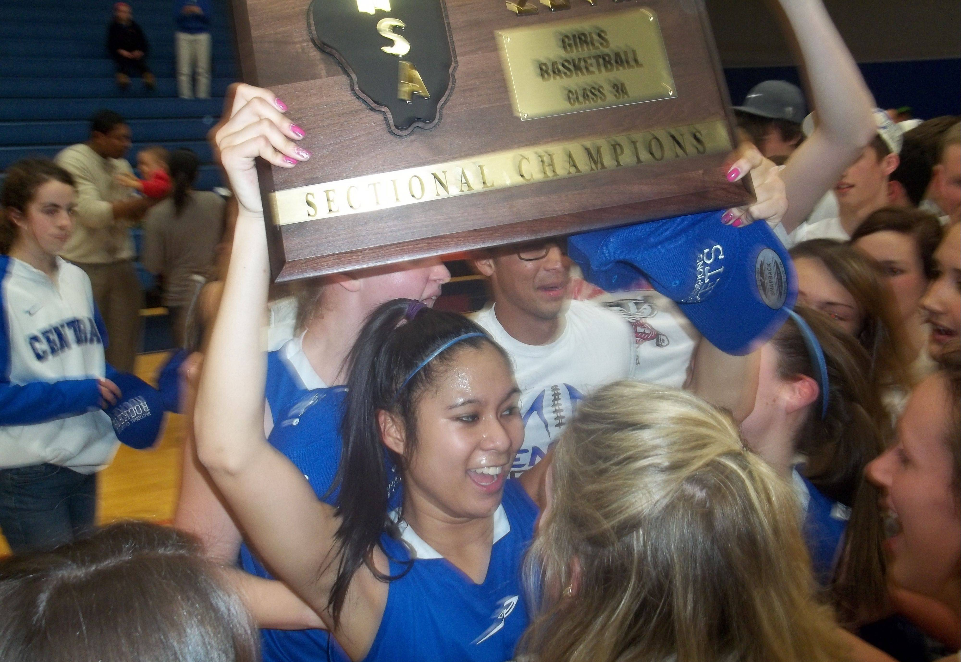 Burlington Central senior Camille Delacruz celebrates with the Class 3A sectional championship plaque Thursday night after the Rockets' 49-26 win over Sterling in the championship game at Genoa-Kingston.