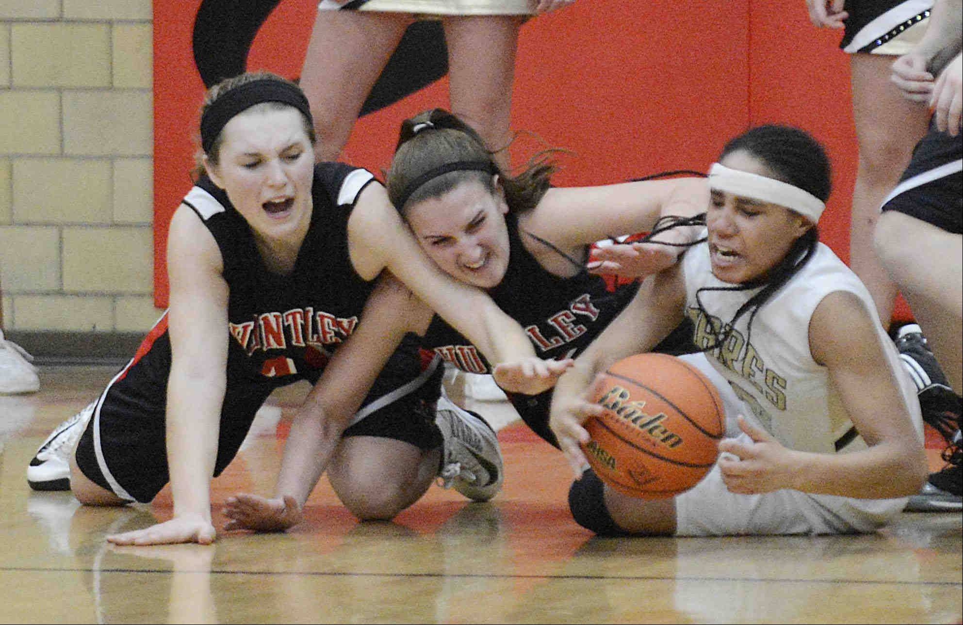 Huntley�s Sam Andrews, left, and Haley Ream pressure Streamwood�s Deja Moore in the closing seconds of the game.