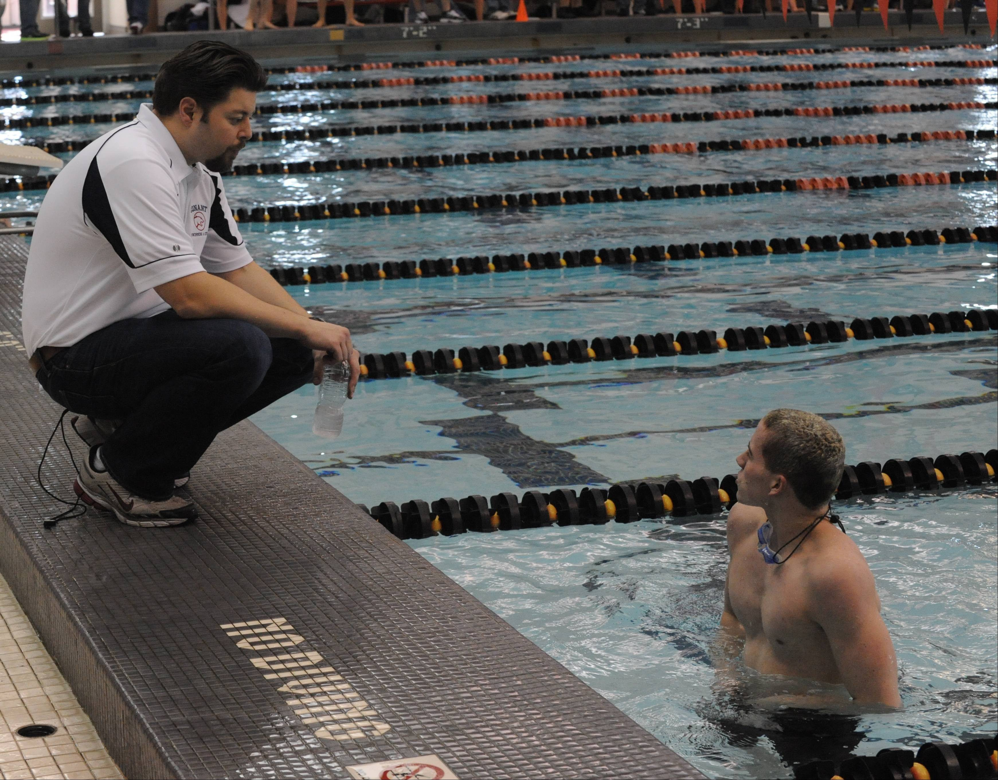 Conant's Jonathon Burke has a word with coach Brian Drenth after cooling down following his MSL-winning effort in the 500 freestyle at Barrington.