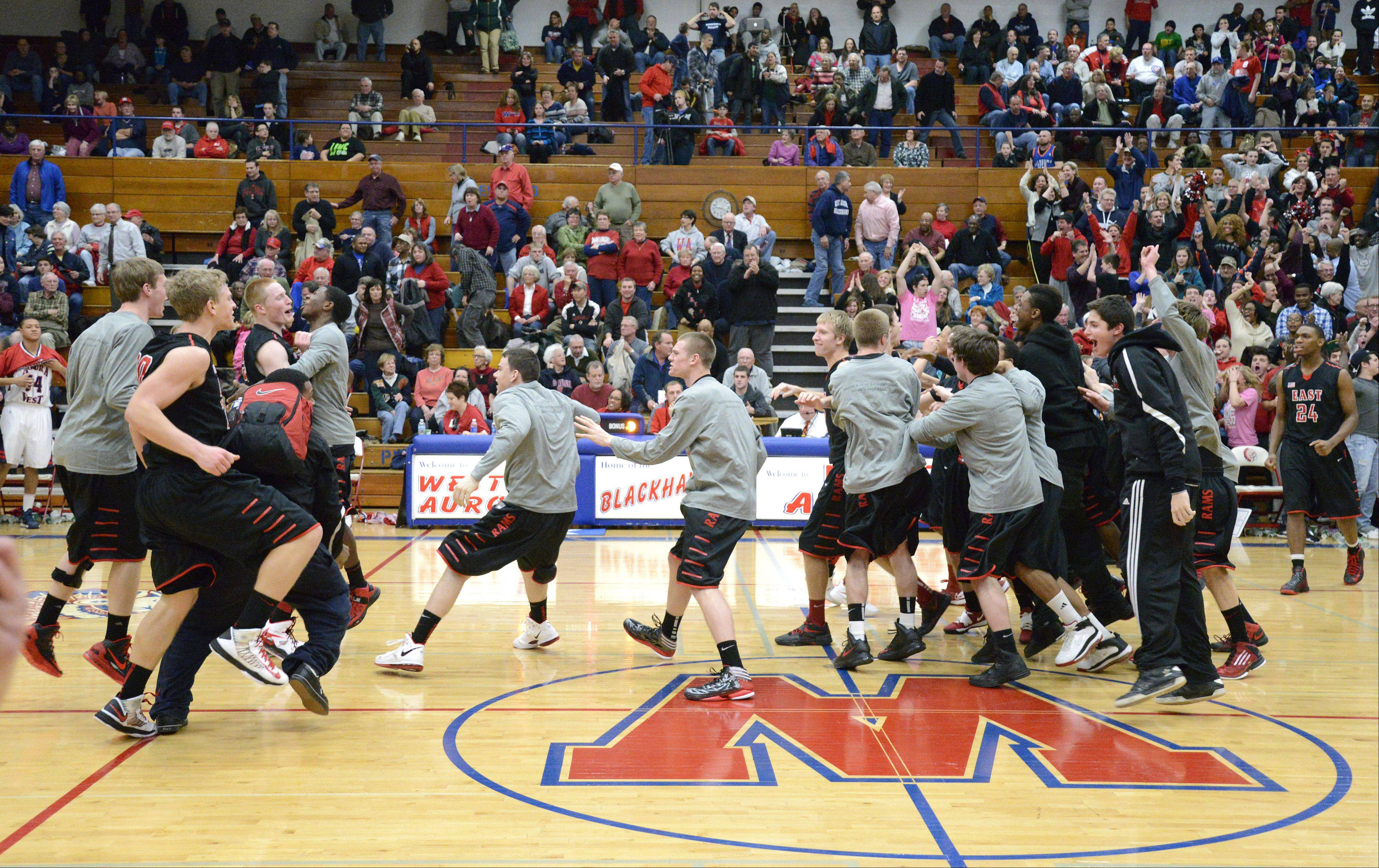 Glenbard East teammates storm the floor after their win over West Aurora in double overtime.