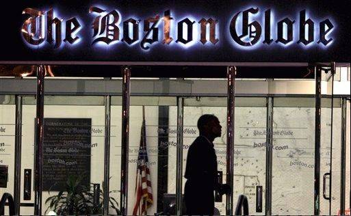 A security guard walks past the entrance of The Boston Globe building in the Dorchester neighborhood of Boston.