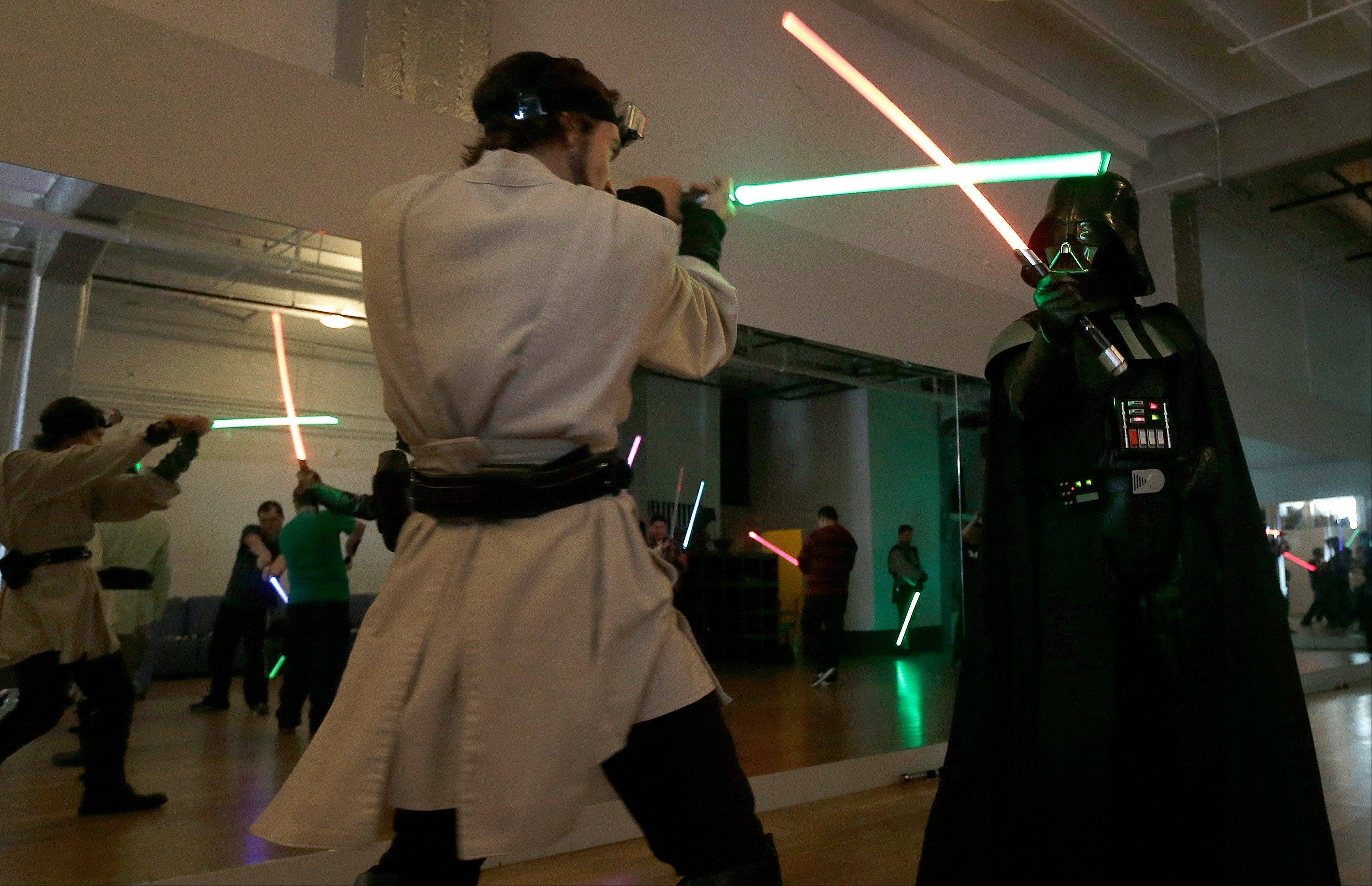 Golden Gate Knights instructor Alain Block, left, and Gary Ripper, dressed as Darth Vader, demonstrate light saber moves during class in San Francisco on Sunday.