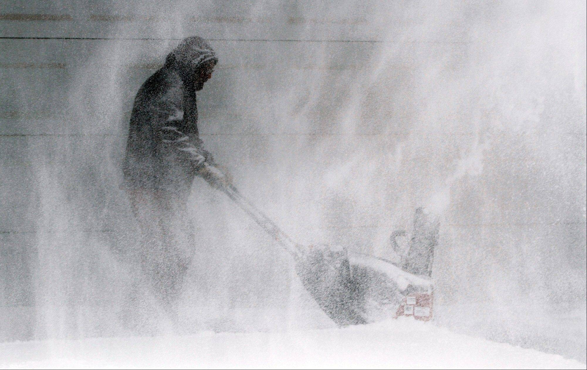 Tom McReynolds clears snow from a neighbors' house in Wichita, Kans., Thursday, Feb. 21, 2013. Kansas was the epicenter of the winter storm, with parts of Wichita buried under 13 inches of still-falling snow, but winter storm warnings stretched eastern Colorado through Illinois.