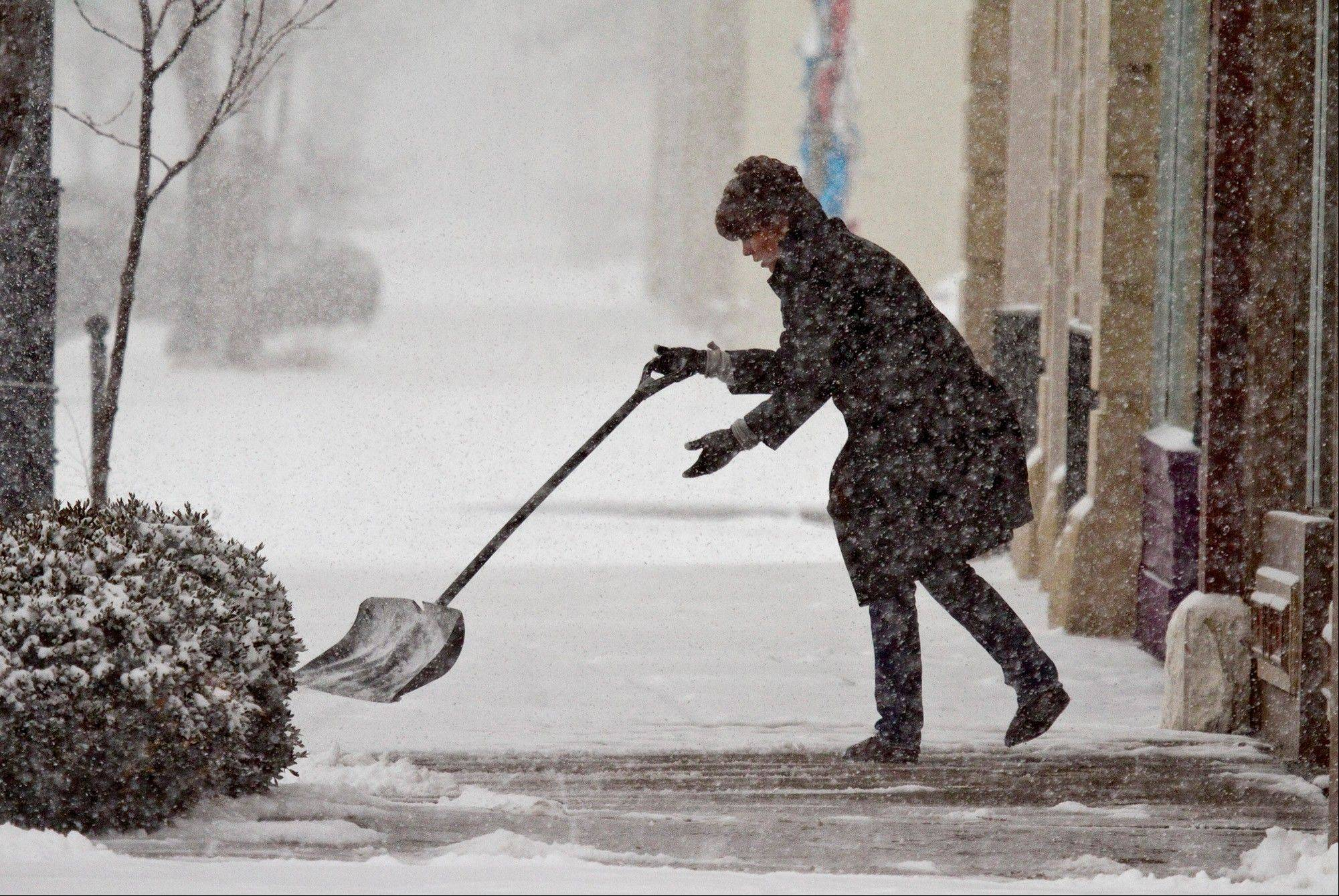 Roxanne Aubrey shovels snow from the walk in front of her beauty salon in Wichita, Kan. Wednesday, Feb. 20, 2013.
