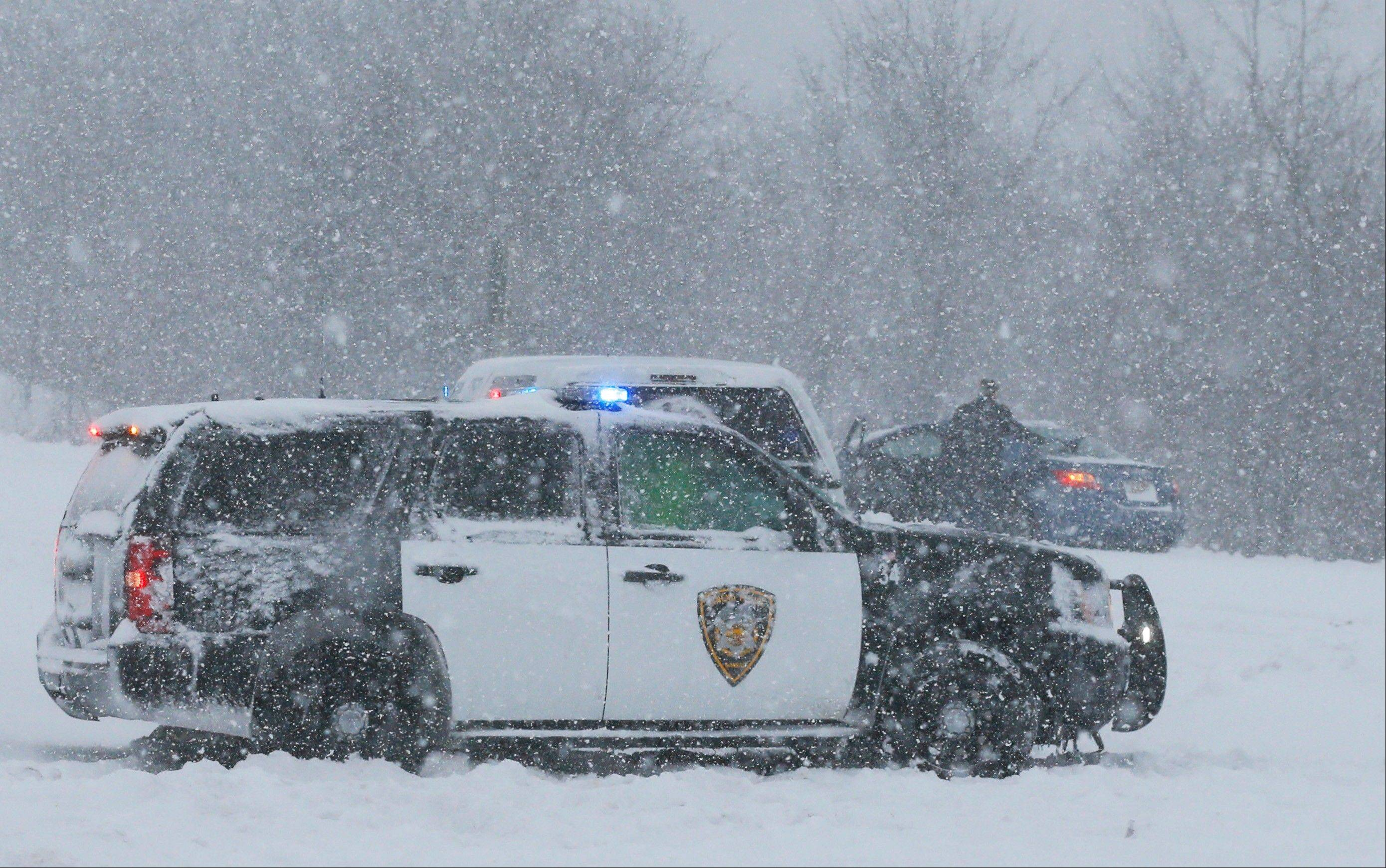A Lenexa Police vehicle stops to aid motorists stuck on a ramp to I-35 in Lenexa, Kan., Thursday, Feb. 21, 2013. The Kansas Turnpike Authority encouraged drivers to stay off the turnpike entirely; it runs from Oklahoma to Kansas City. There was virtually zero visibility on the turnpike early Thursday. And I-70 and other major highways in Kansas were snowpacked and icy, according to the Kansas Department of Transportation. Kansas Gov. Sam Brownback closed executive offices, except for essential personnel. He urged residents to have an extra cup of coffee, get out a board game and play with their children.
