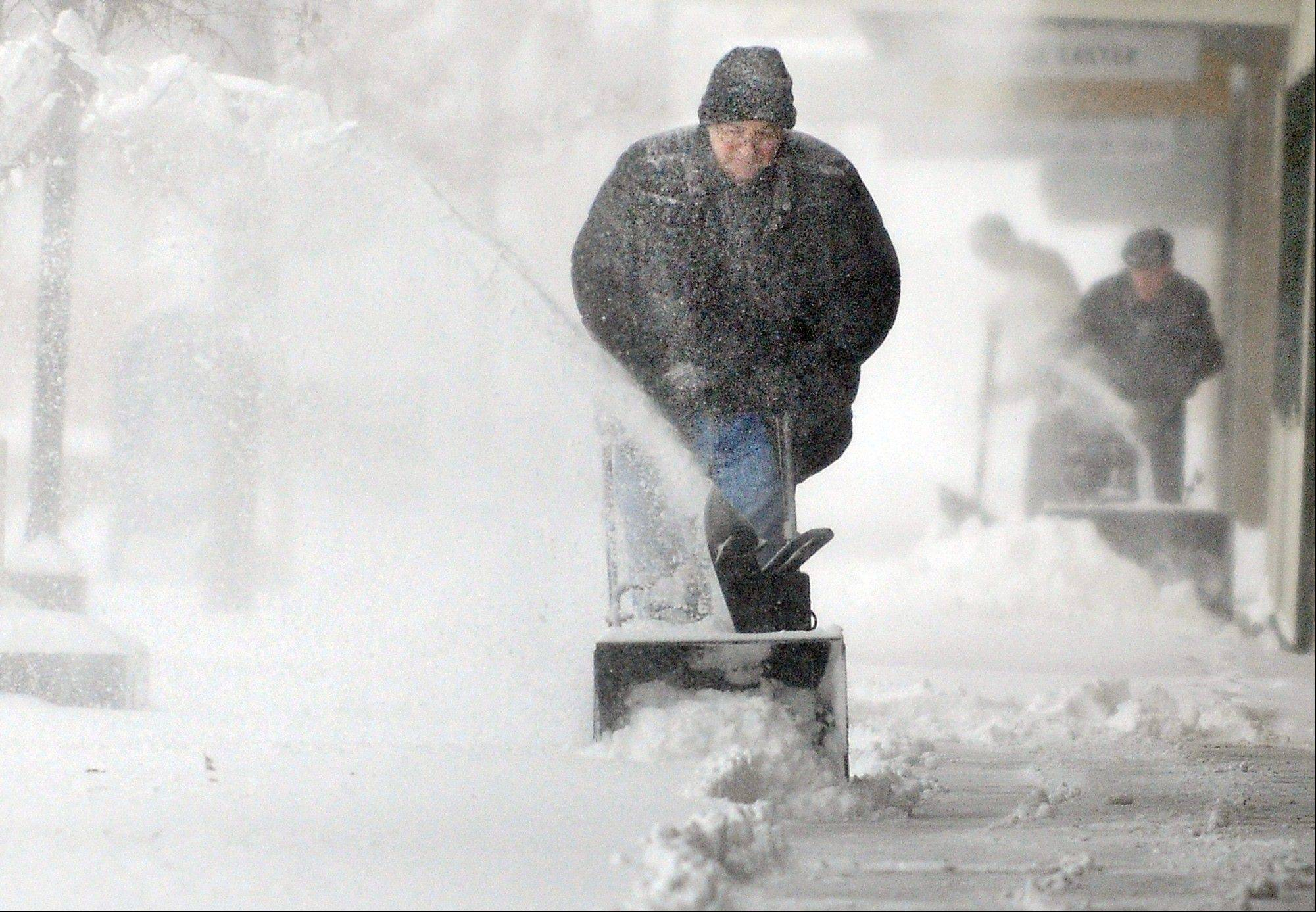 Chuck Carroll, center, uses a snowblower to clear the sidewalk in front of his business in downtown Salina, Kan. Thursday morning Feb. 21, 2013. Carroll said he had cleared the sidewalk Wednesday night and expected to remove snow at least once more Thursday.