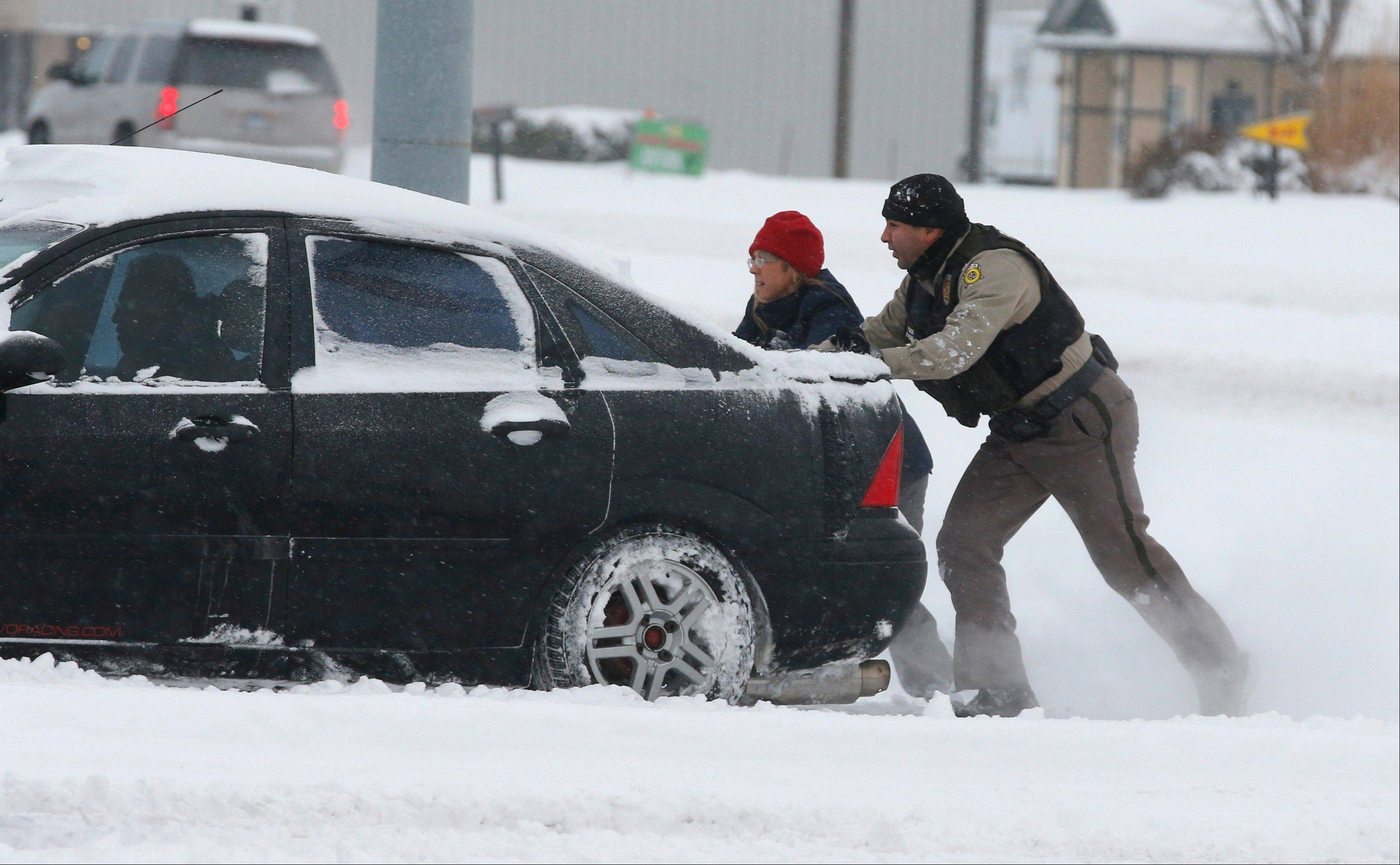 A Sedgwick County Sheriff's deputy helps a stranded motorist in Wichita, Kans. Thursday, Feb 21, 2013, as nearly a foot of snow covered the area. Kansas was the epicenter of the winter storm, with parts of Wichita buried under 13 inches of still-falling snow, but winter storm warnings stretched eastern Colorado through Illinois.