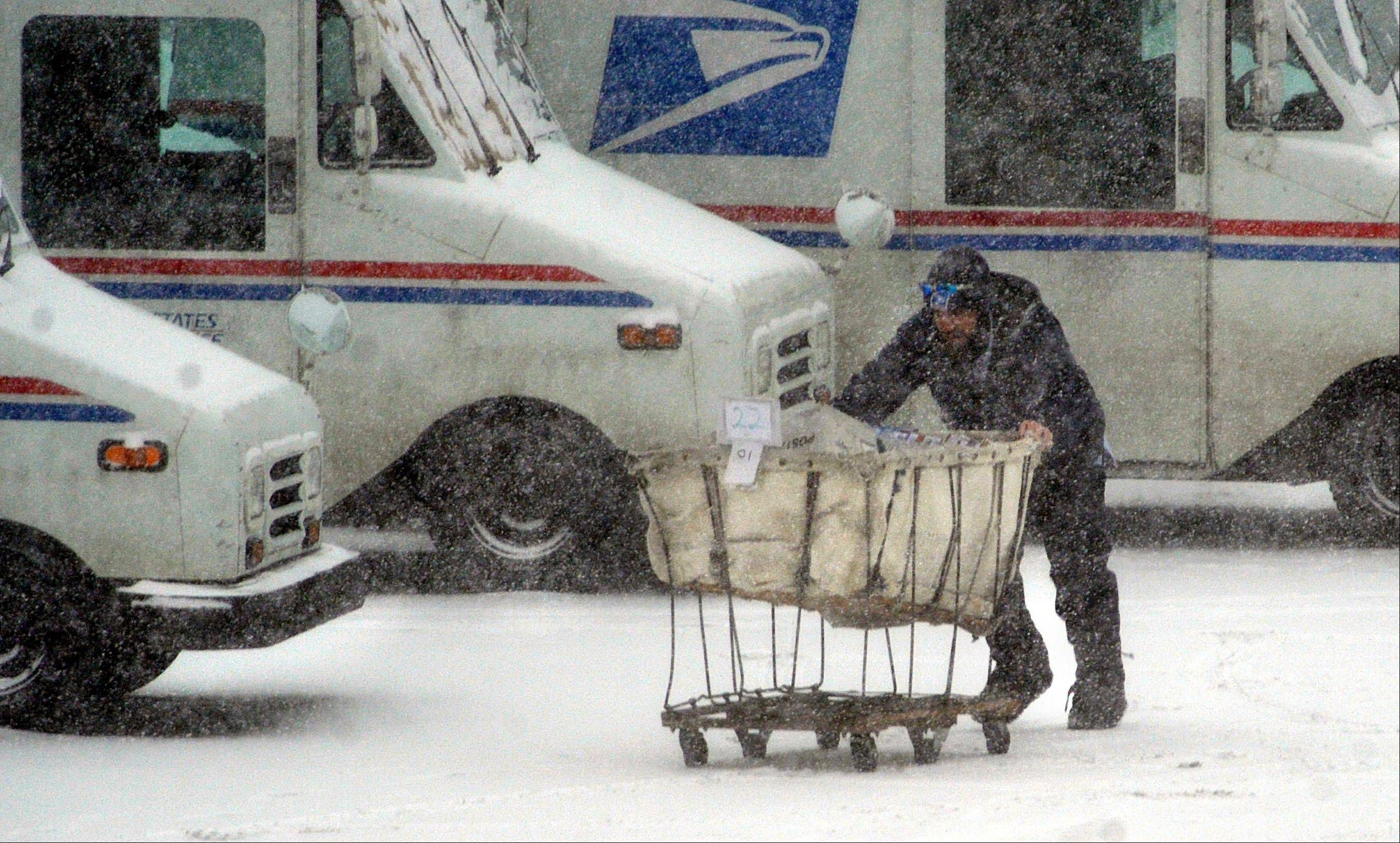 U.S. Postal Service employee Craig Conner tries to navigate a mail cart to his vehicle Thursday morning Feb. 21, 2013 in downtown St. Joseph, Mo., shortly after the snowstorm started. Winter storm warnings were issued from eastern Colorado through Illinois Thursday.
