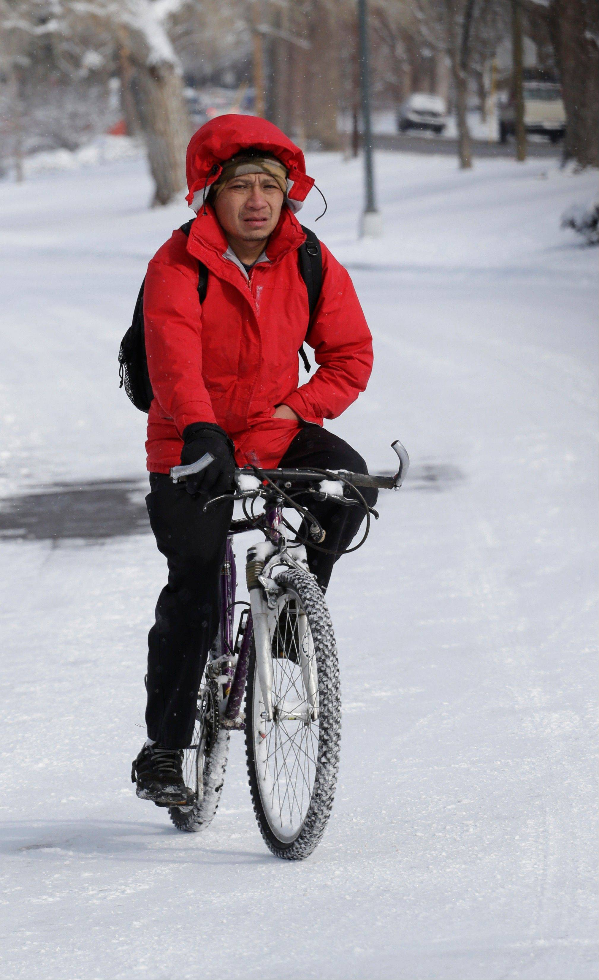 Hector Valdez rides his bike through the snow in Denver on Thursday, Feb. 21, 2013. A fast moving winter storm passed through Colorado Wednesday night and Thursday morning dropping as much as a foot of snow in areas of the state.