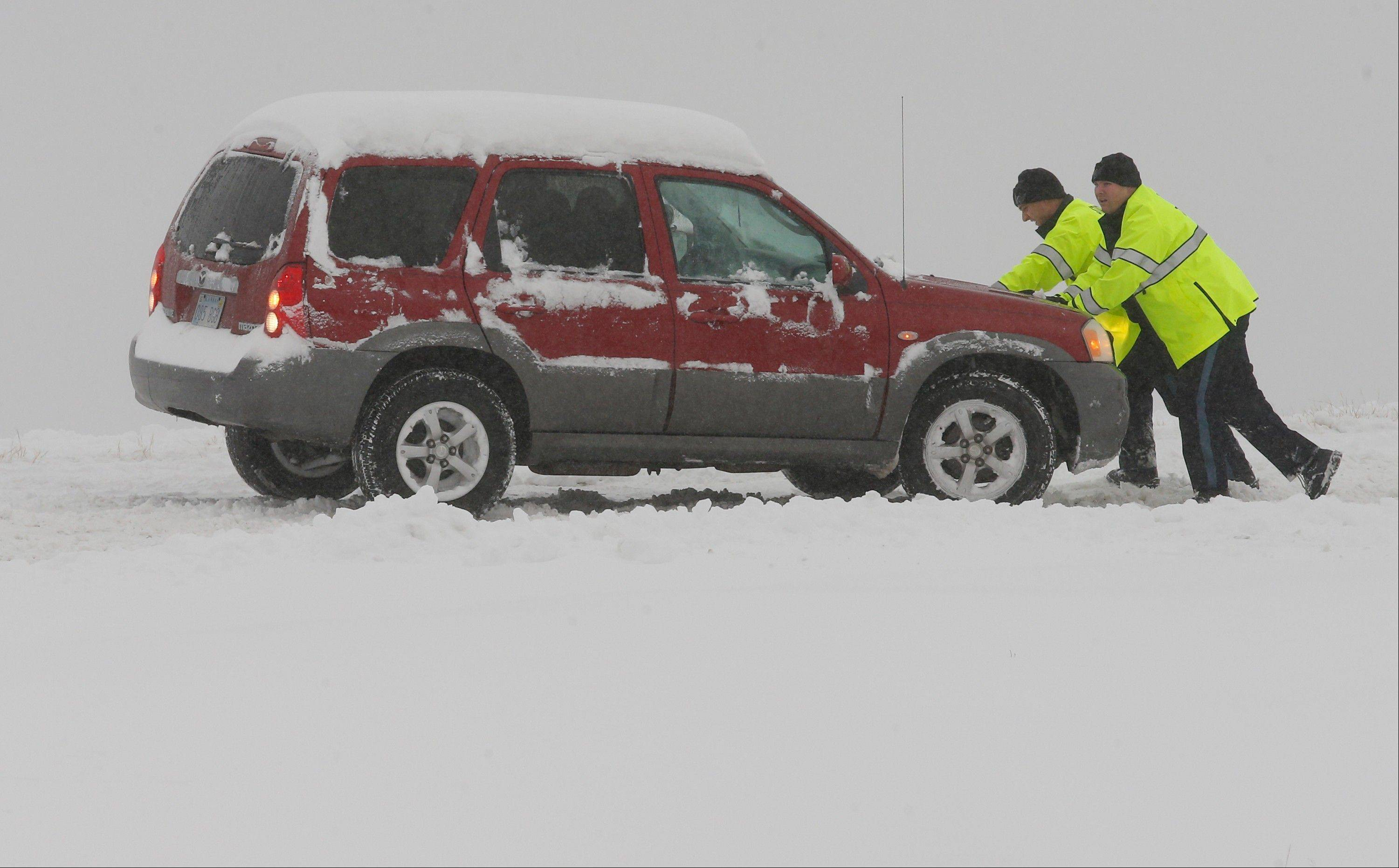 Motorist attempt to push a car back on the road in Wichita, Kans. Thursday, Feb 21, 2013. Numerous cars and trucks were stuck or off the road as nearly a foot of snow fell across the area. Kansas was the epicenter of the winter storm, with parts of Wichita buried under 13 inches of still-falling snow, but winter storm warnings stretched eastern Colorado through Illinois.