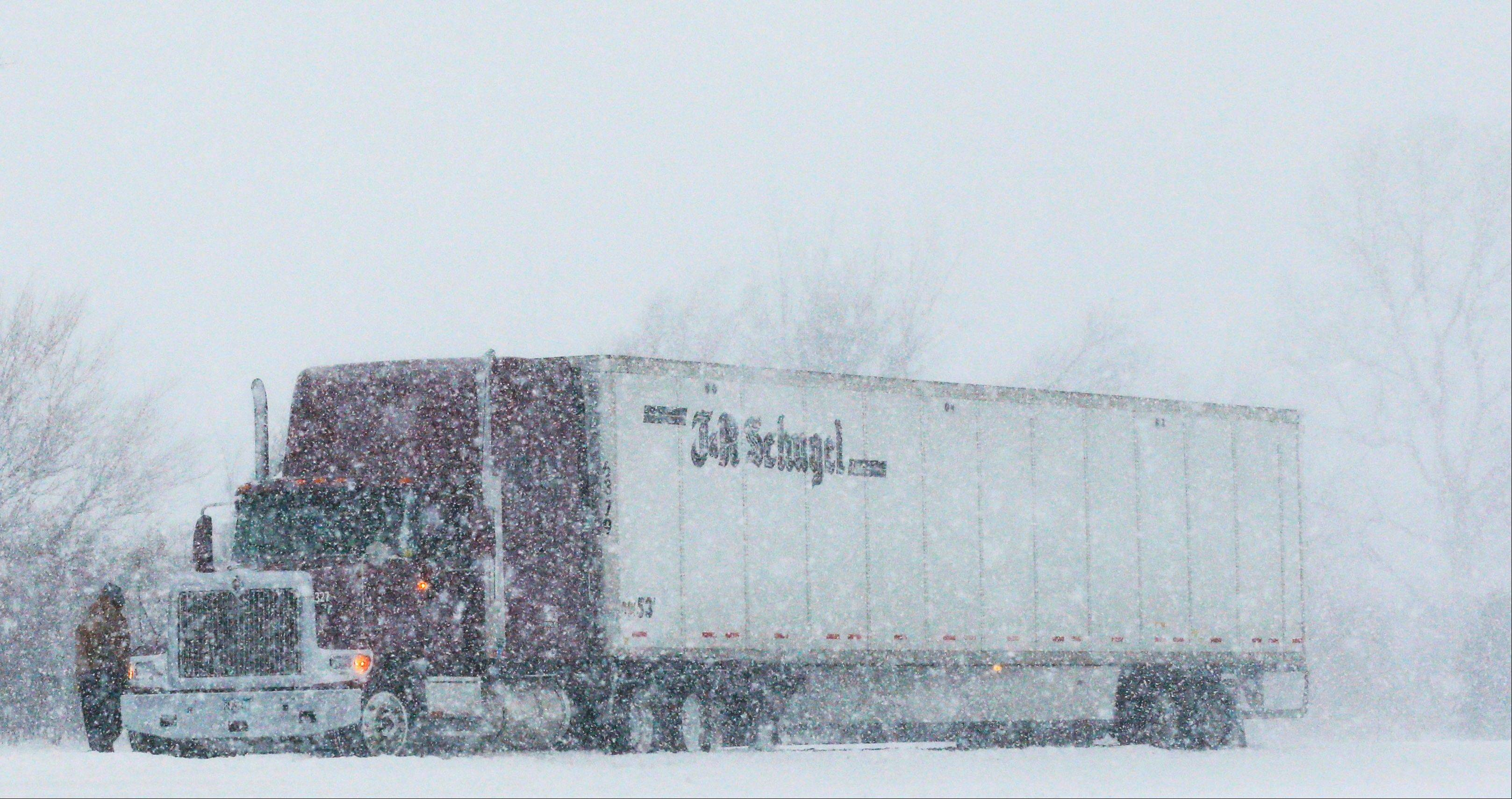 A trucker stops in almost whiteout conditions along K-10 highway near Eudora, Kan., Thursday, Feb. 21, 2013. The Kansas Turnpike Authority encouraged drivers to stay off the turnpike entirely; it runs from Oklahoma to Kansas City. There was virtually zero visibility on the turnpike early Thursday. And I-70 and other major highways in Kansas were snowpacked and icy, according to the Kansas Department of Transportation. Kansas Gov. Sam Brownback closed executive offices, except for essential personnel. He urged residents to have an extra cup of coffee, get out a board game and play with their children.