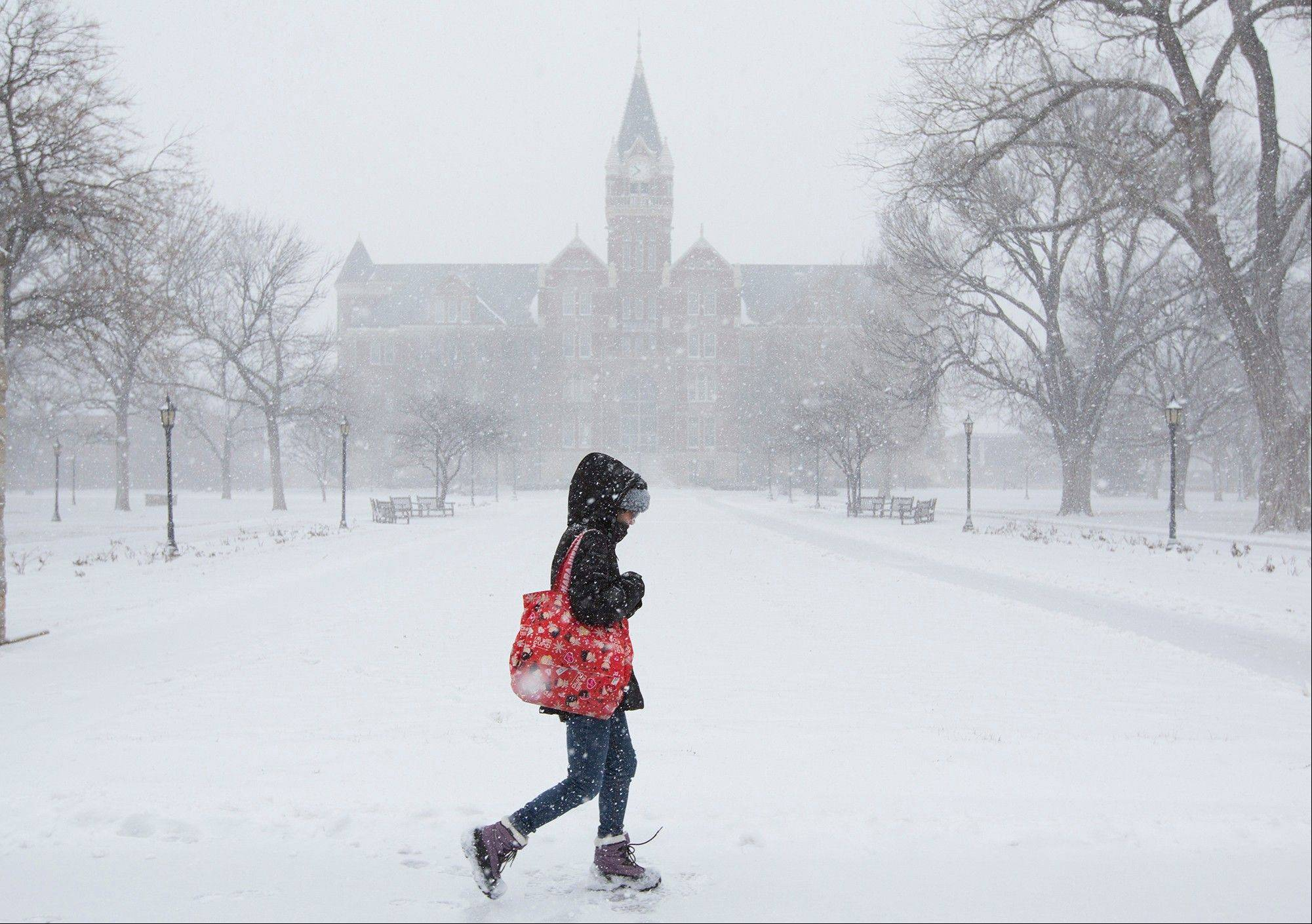 A student makes her way across the campus of Friends University in Wichita, Kan. as heavy snow falls on Wednesday morning, Feb. 20, 2013. A large winter storm moved in over the early morning hours and is expected to last until Thursday evening.