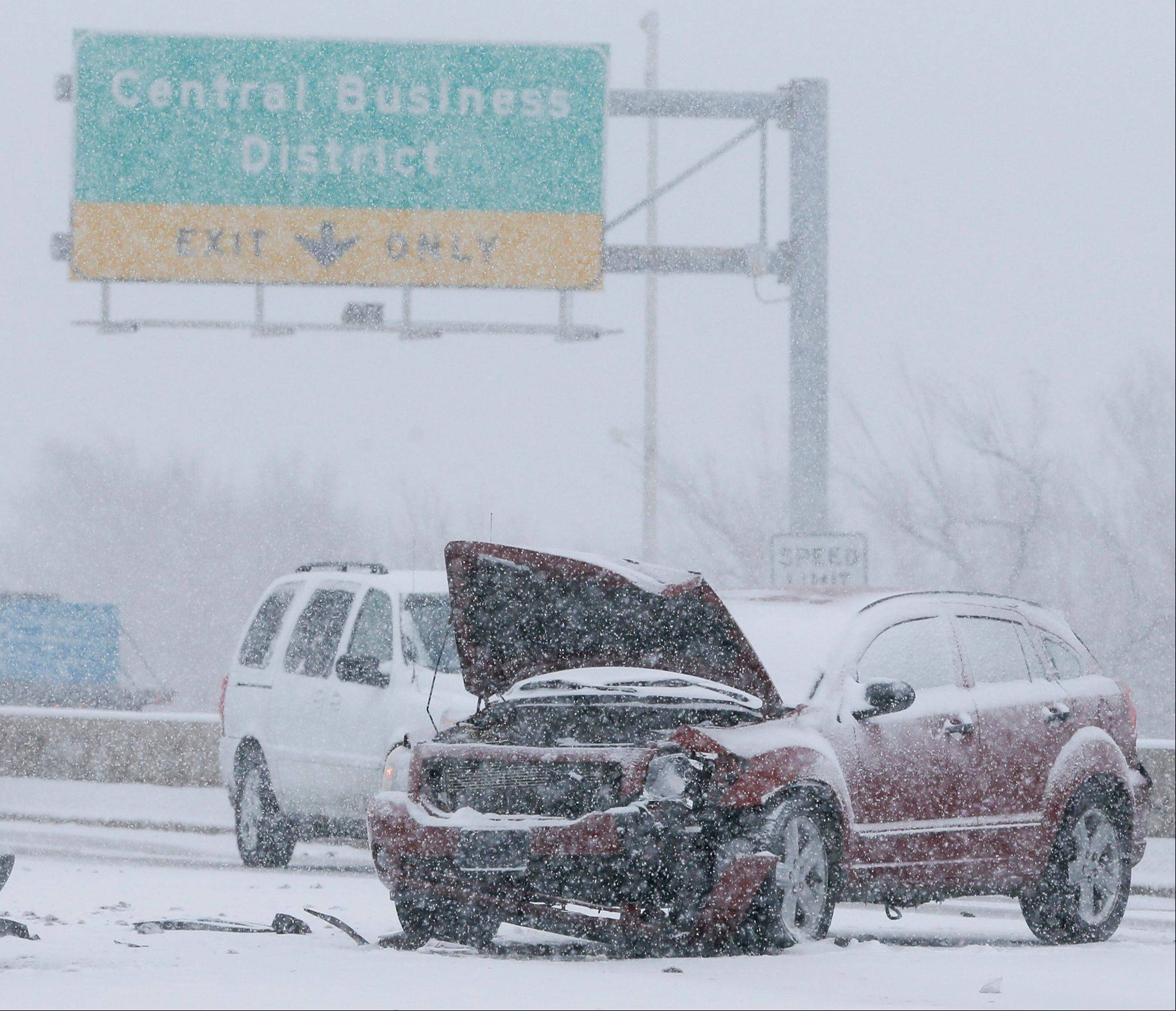 A wrecked car sits in the middle of US Highway 54 near downtown Wichita, Kan. as heavy snow falls on Wednesday morning, Feb. 20, 2013. A large winter storm moved in over the early morning hours and is expected to last until Thursday evening.