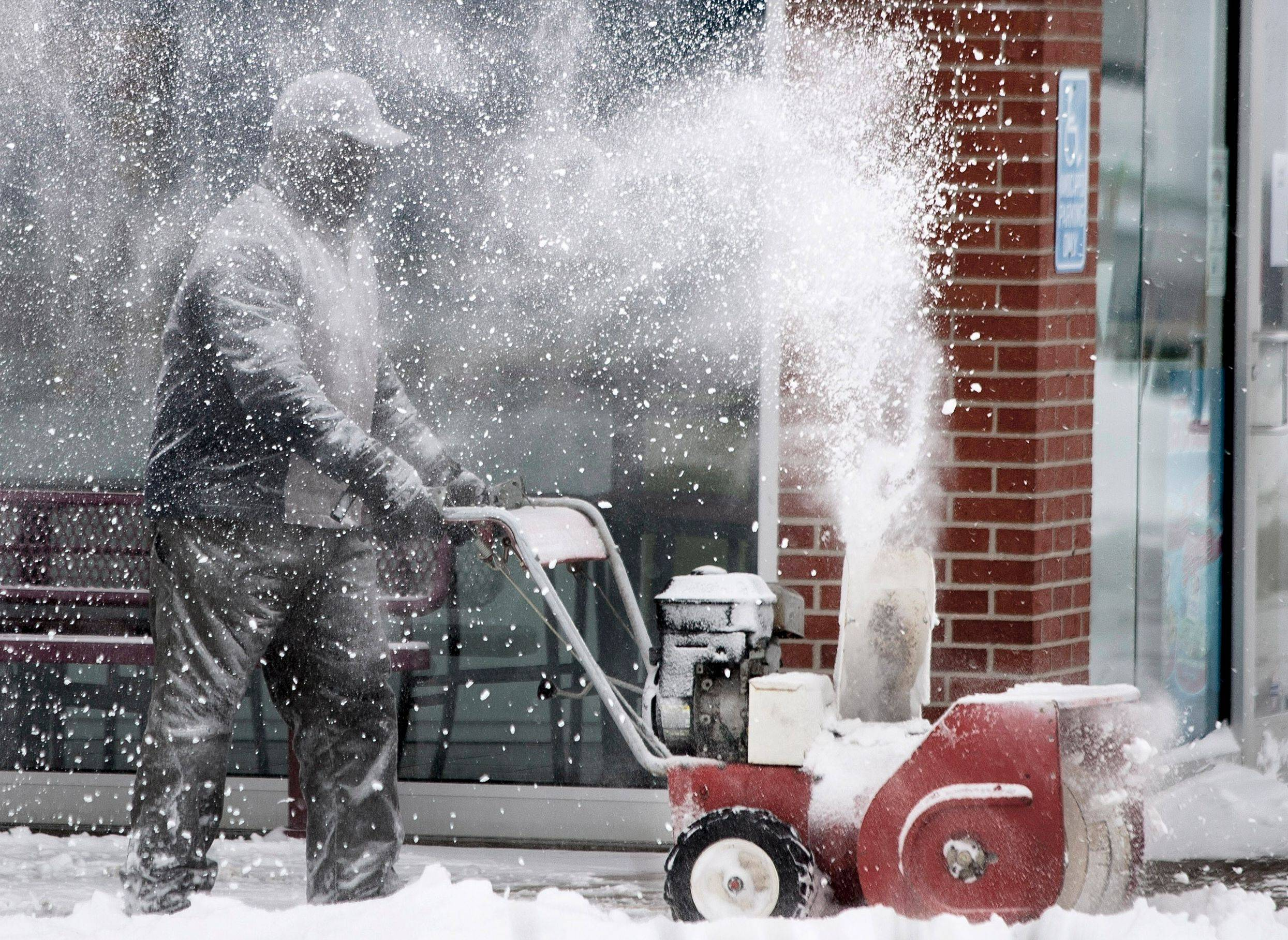 While covering himself with snow, a man uses a snow thrower to clear the sidewalk of a business during the morning hours Thursday, Feb. 21, 2013 in Topeka, Kan. Kansas was the epicenter of the winter storm, with parts of the state buried under 14 inches of powdery snow, but winter storm warnings stretched from eastern Colorado through Illinois.