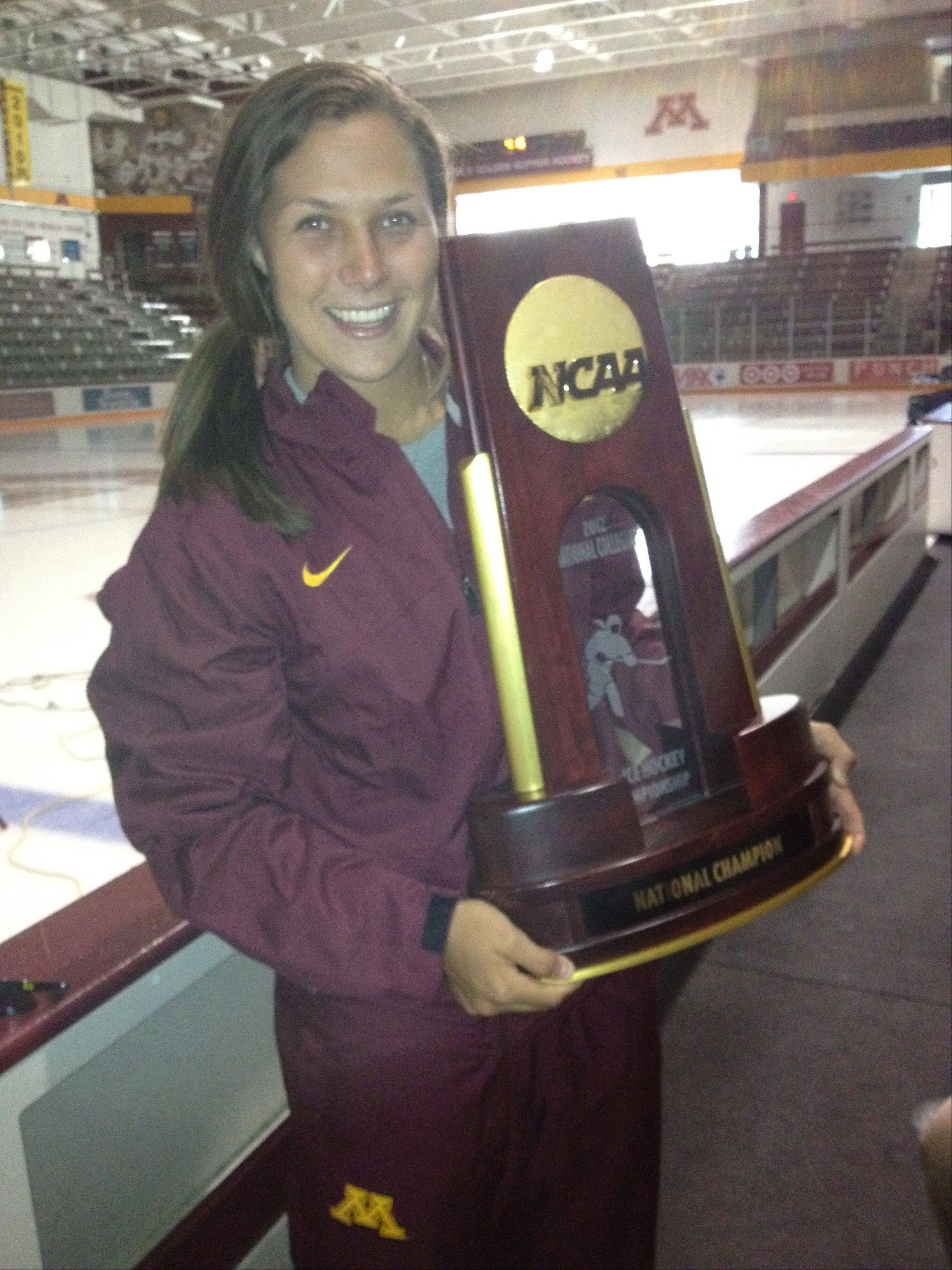 Buffalo Grove native Megan Bozek, co-captain of the undefeated University of Minnesota women's ice hockey team, holds the 2012 National Championship trophy.