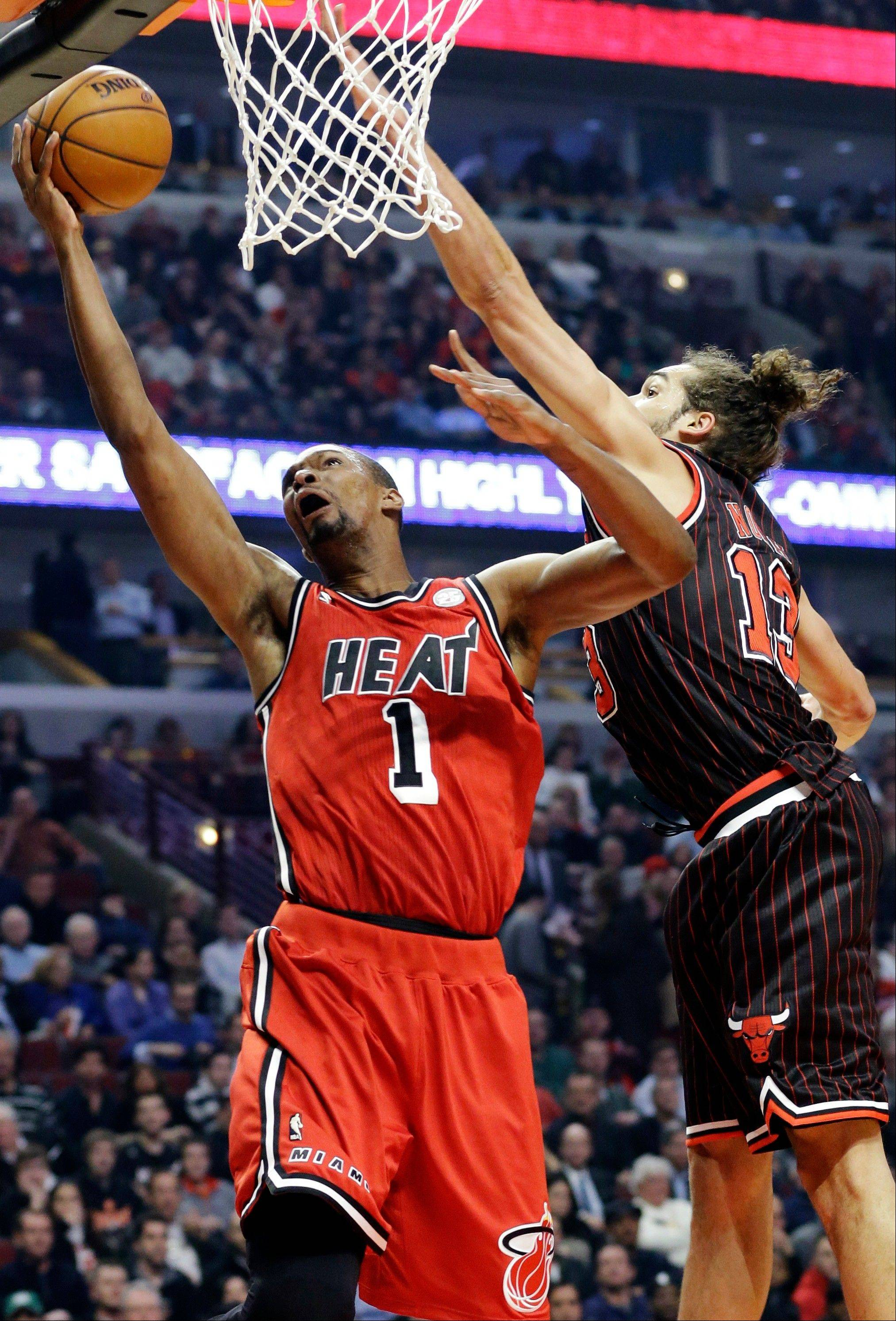 Heat center Chris Bosh (1) drives to the basket against Chicago Bulls center Joakim Noah during the first half of an NBA basketball game in Chicago, Thursday, Feb. 21, 2013.