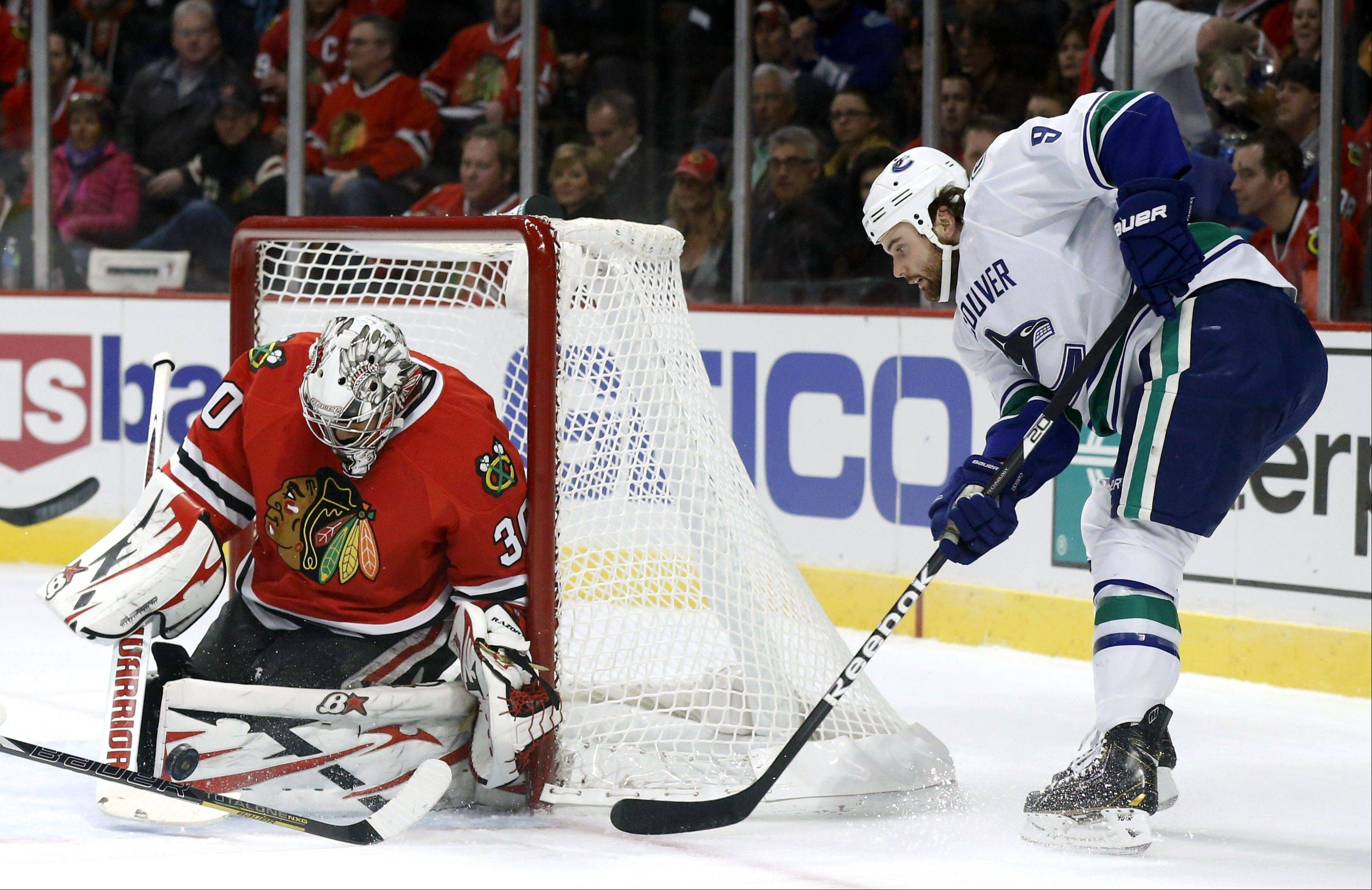 Vancouver Canucks right wing Zack Kassian, who started the season with the Chicago Wolves, tries to get off a shot Tuesday against Blackhawks goalie Ray Emery.