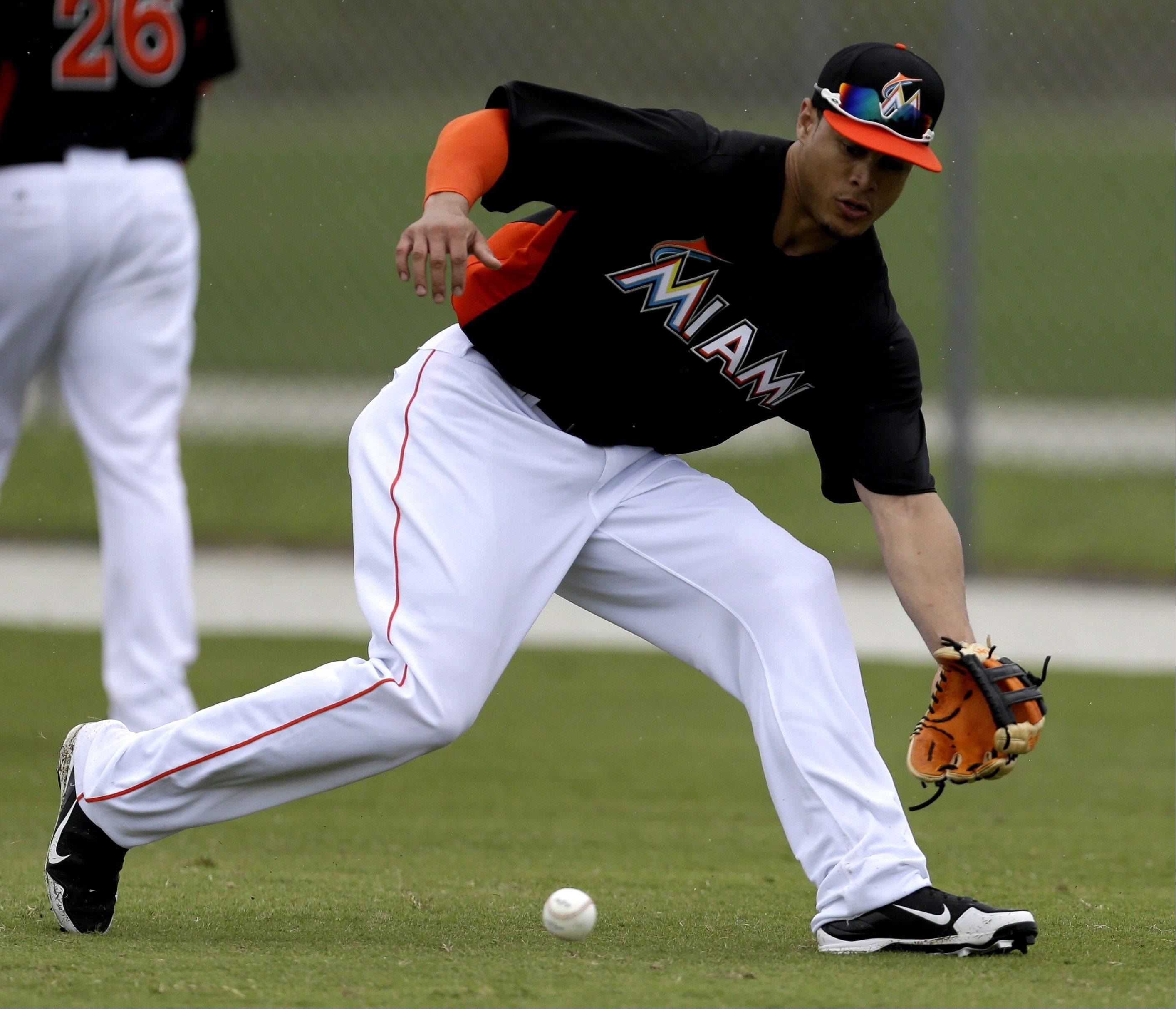 Miami Marlins right fielder Giancarlo Stanton fields a groundball in the outfield during a spring-training workout in Jupiter, Fla.