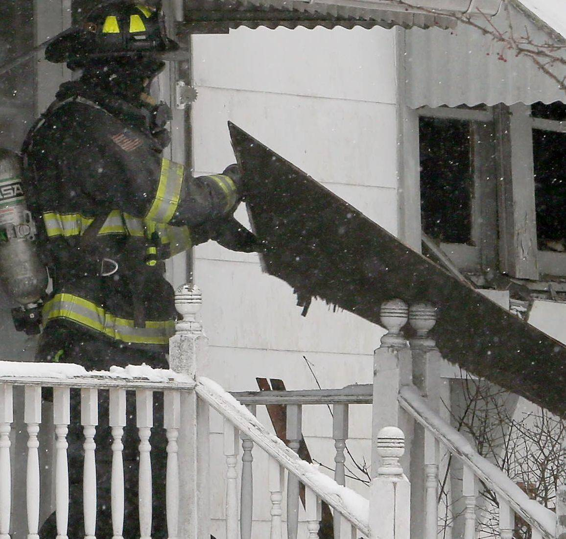 Firefighters work at the scene of a house fire that killed a woman Friday in West Chicago.