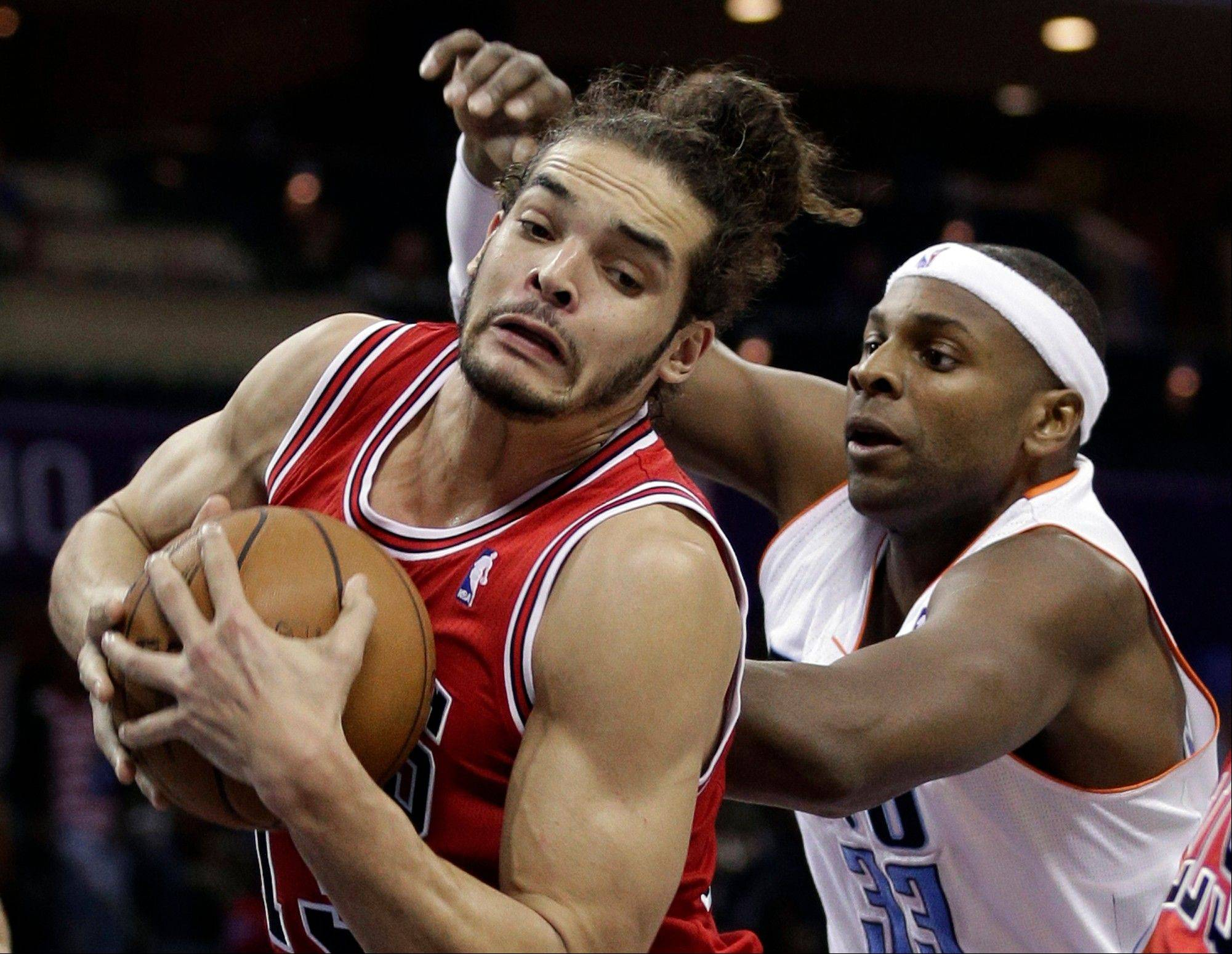 Chicago Bulls' Joakim Noah, left, grabs a rebound as Charlotte Bobcats' Brendan Haywood, right, defends during the first half of an NBA basketball game in Charlotte, N.C., Friday, Feb. 22, 2013. (AP Photo/Chuck Burton)