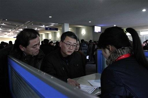 Foreigners speak with sales person at a Koryolink cellphone rental booth, asking about mobile phone service at Pyongyang Airport in Pyongyang, North Korea.