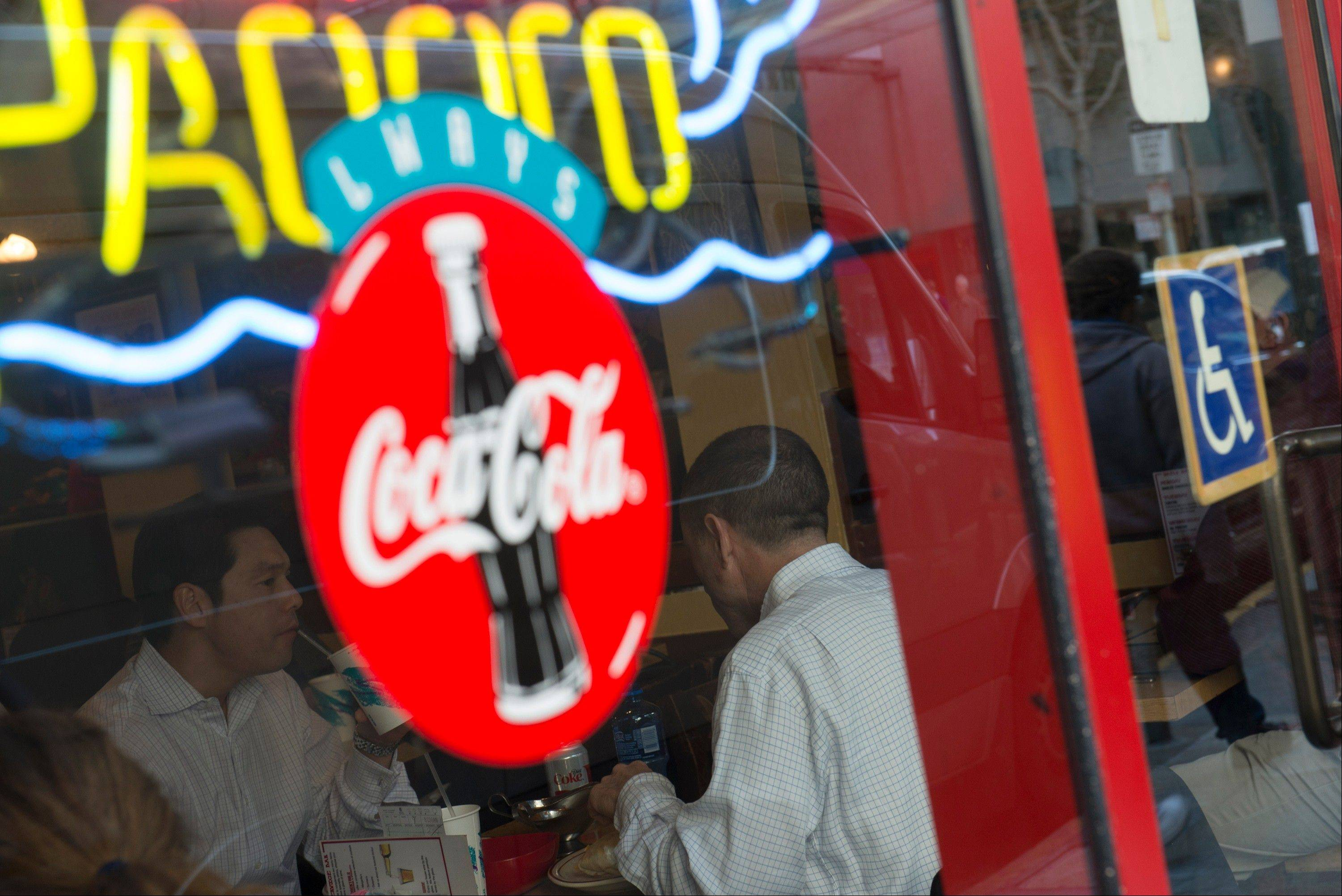 Coca-Cola Co. signage is displayed the window of a restaurant as patrons dine in San Francisco.