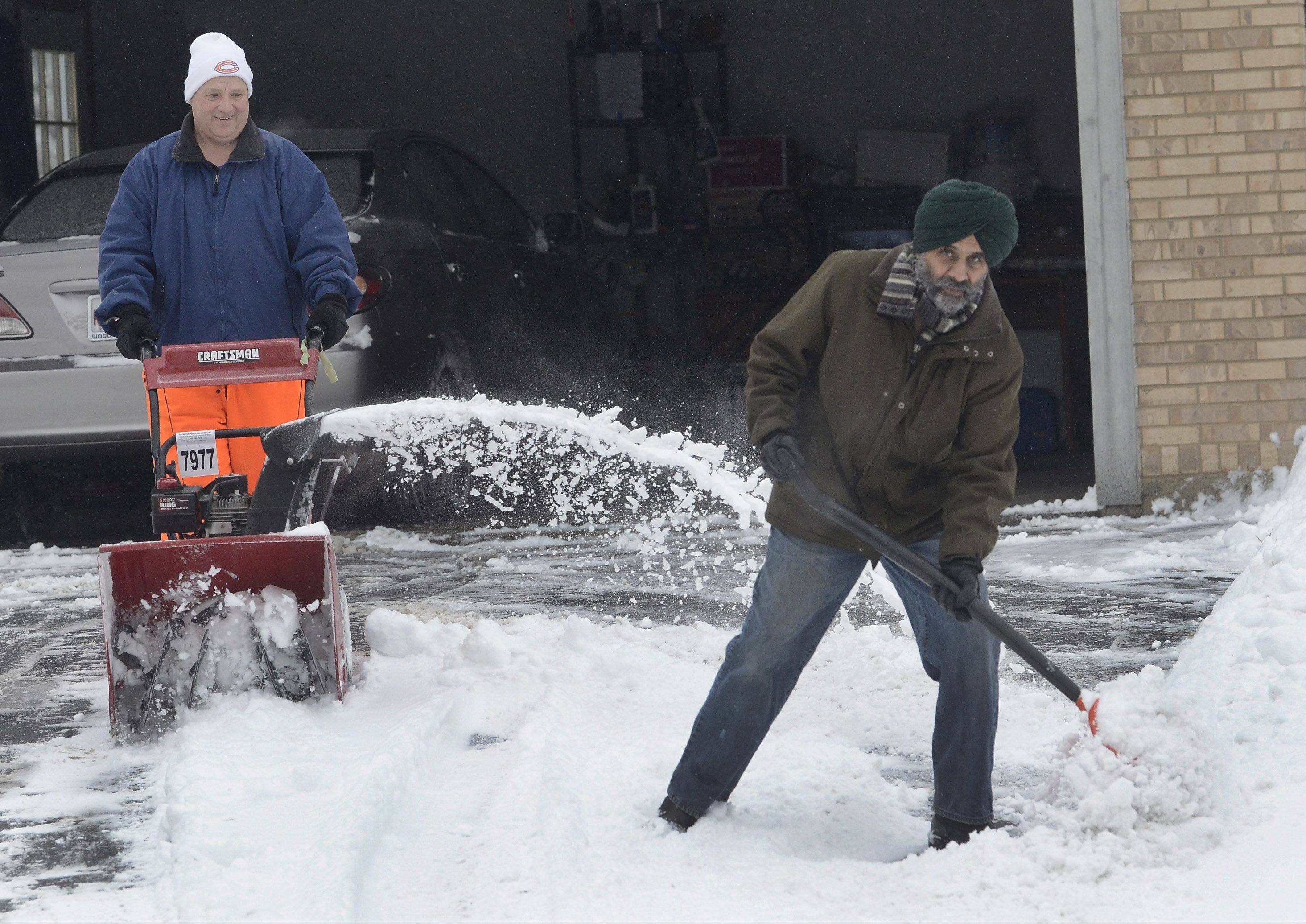 Rich Kuebler, left, helps his neighbor Bhupinder Jhajj clear out his driveway on Carolian Drive in Lake Zurich Friday morning.