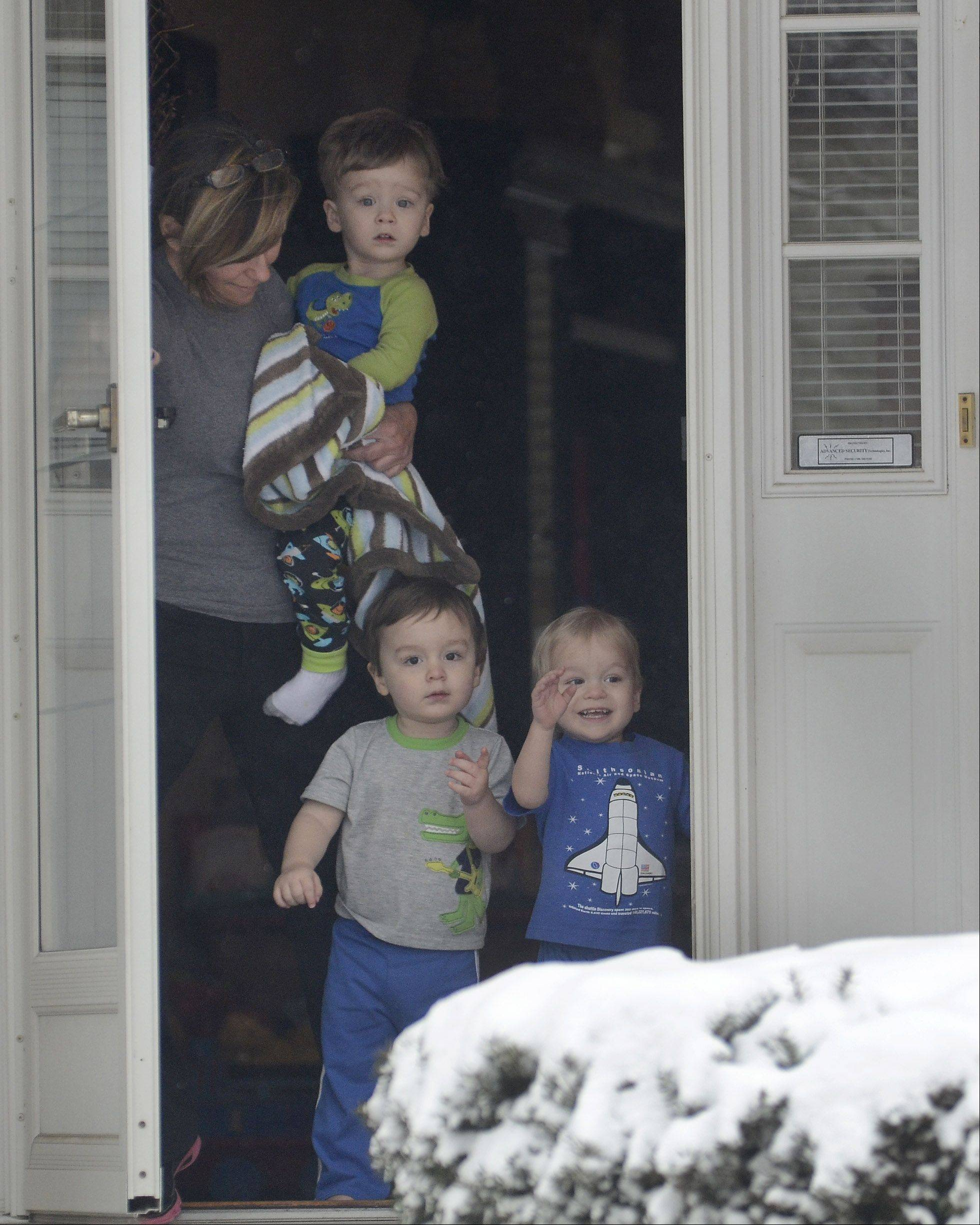 Triplets Nick, Cole and Jake Wojtalewicz wave to their neighbor Rich Kuebler, as he plows a driveway, while Rich's wife Grace Kuebler babysits for the threesome in Lake Zurich Friday morning.