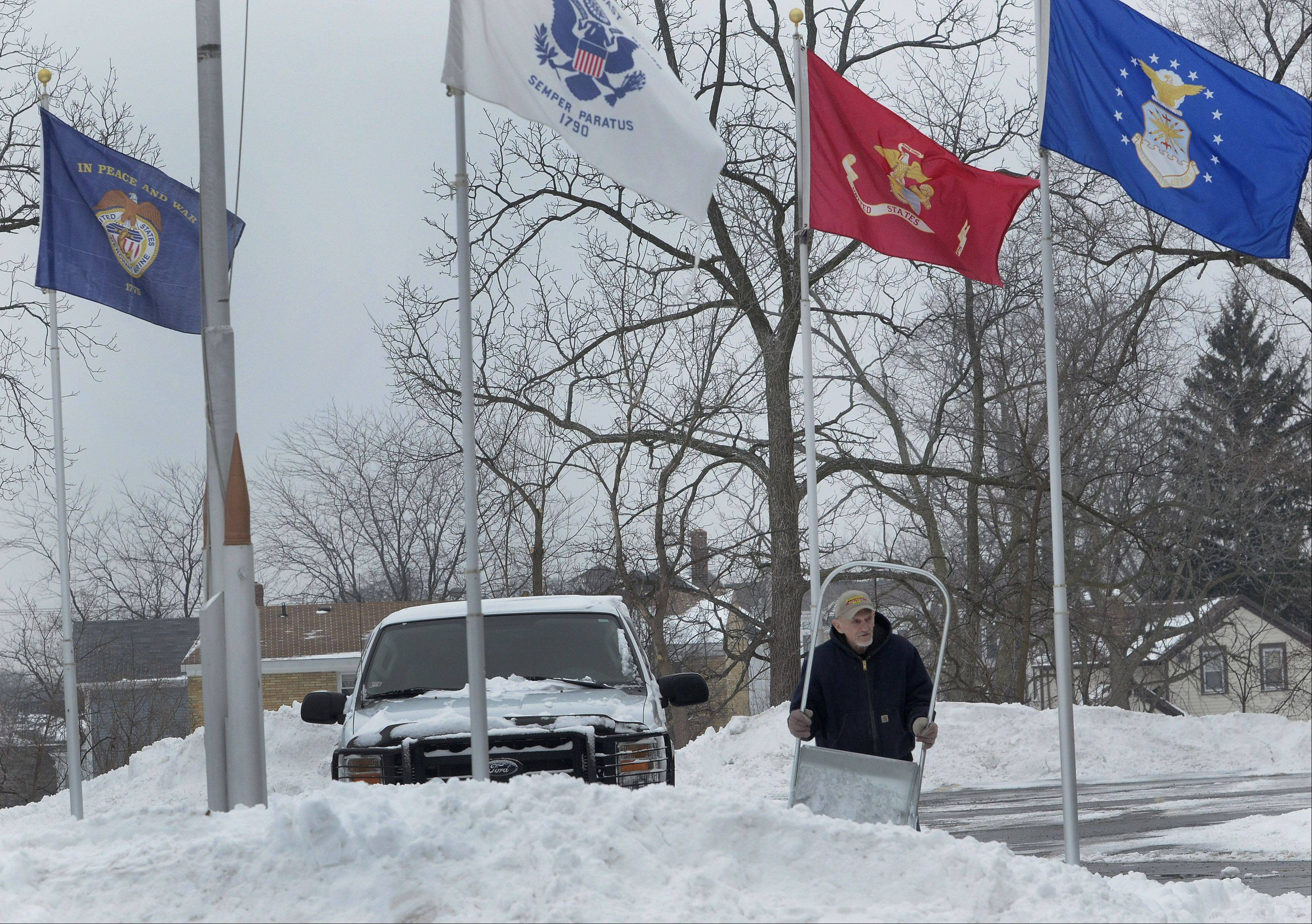 Doug Bartels shovels snow in front of Lake Zurich American Legion Post 964 Friday morning.