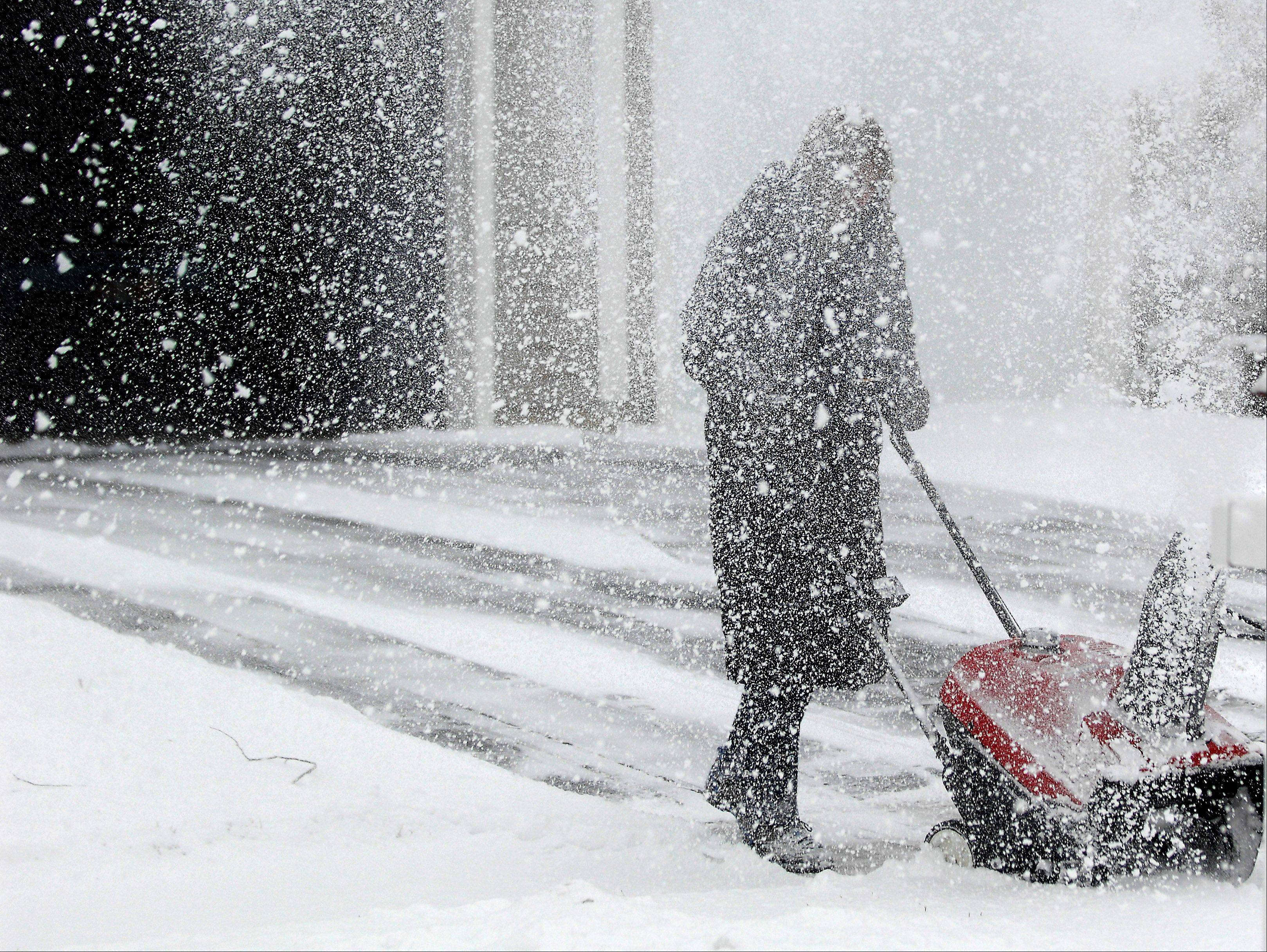 Nancy Flora of Carpentersville whips up a flurry in her driveway while blowing snow Friday morning. The area got less than half of the snow that had been anticipated.