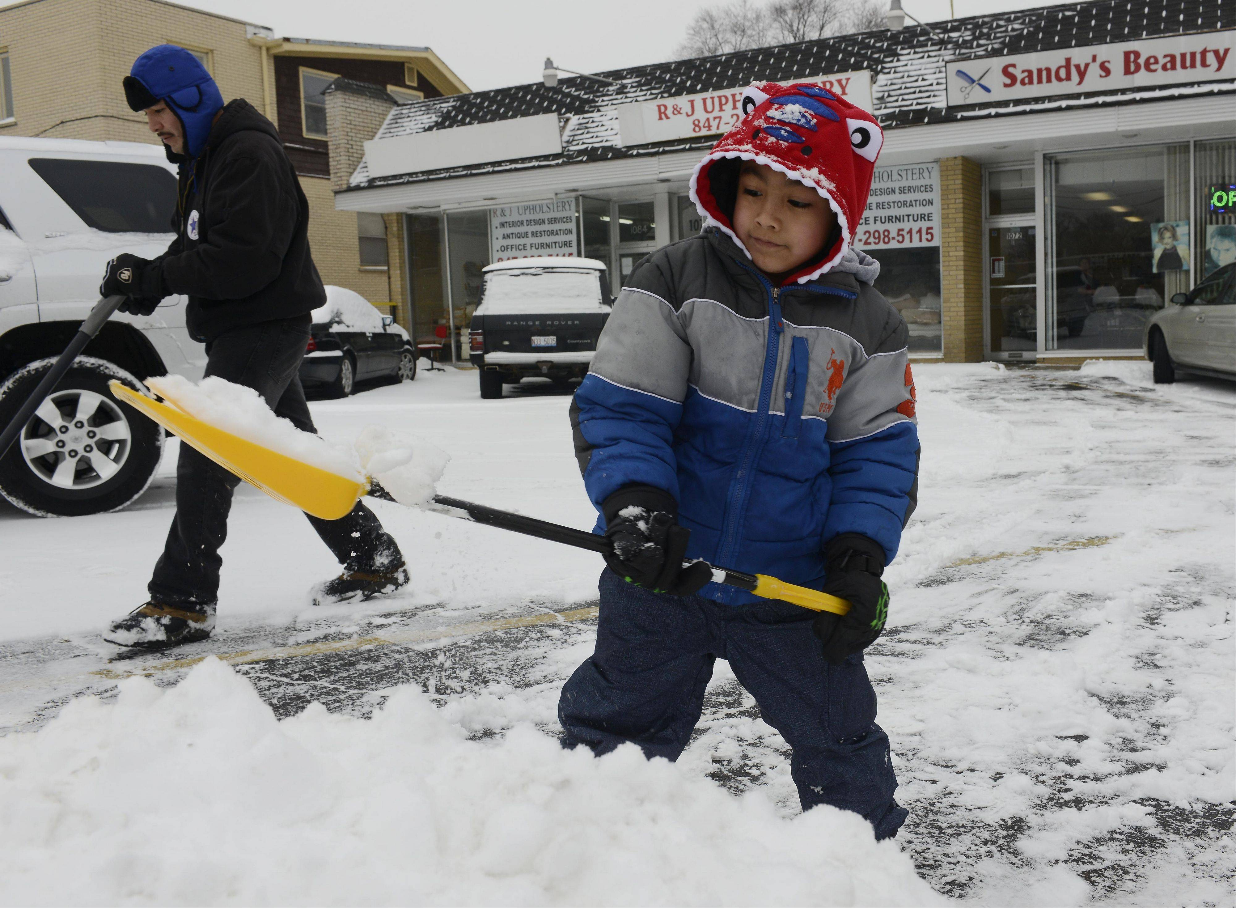 Fernando Velazquez, 5, of Des Plaines helps his dad, Beto, dig out the parking lot of an acquaintance's retail strip along Lee Street in Des Plaines Friday.