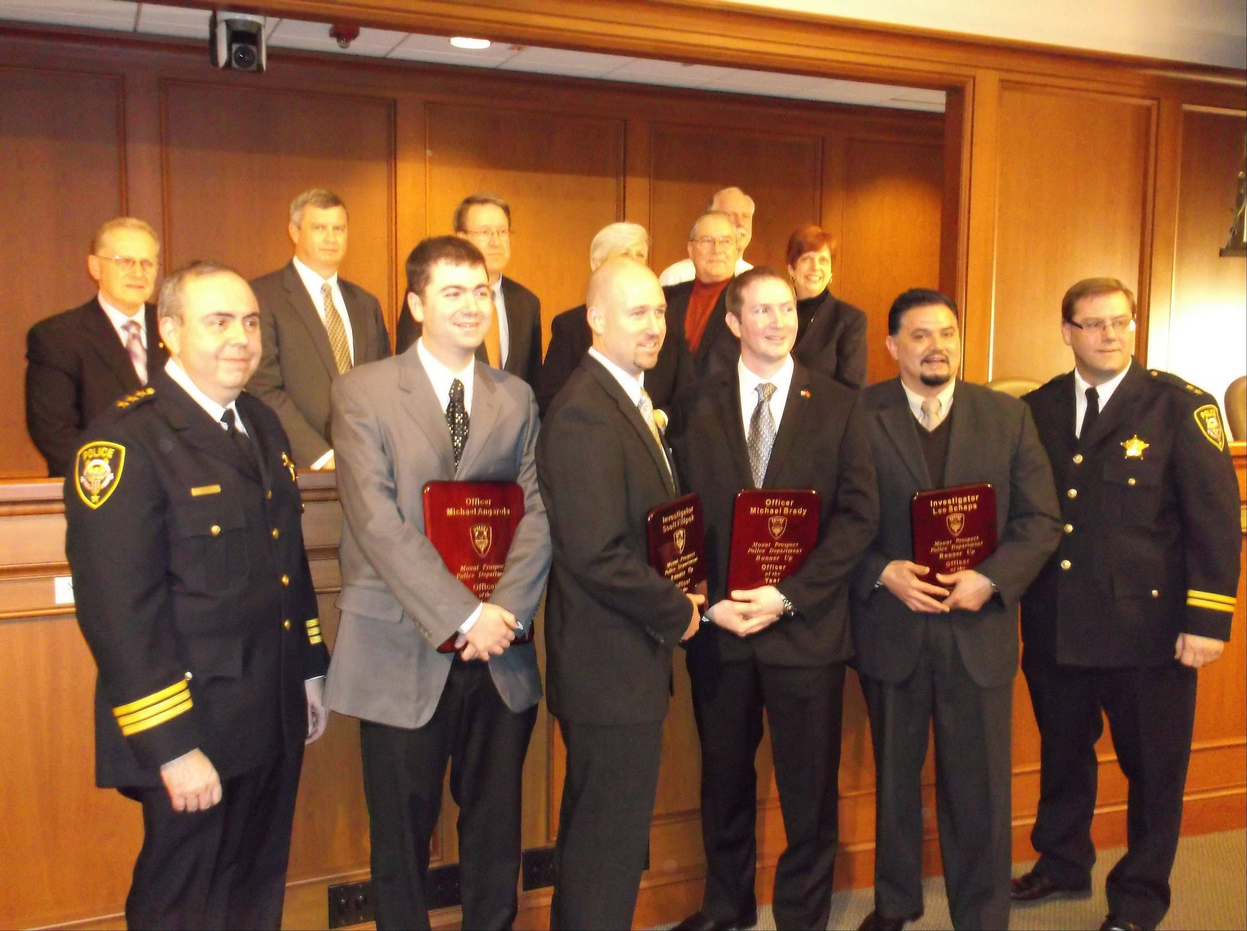 The Mount Prospect Village Board, rear, poses with the officers of the year. In the front row from right are police Chief Mike Semkiu, officers Michael Angarola, Scott Filipek, Michael Brady, Lee Schaps and Deputy Chief Tim Janowick.