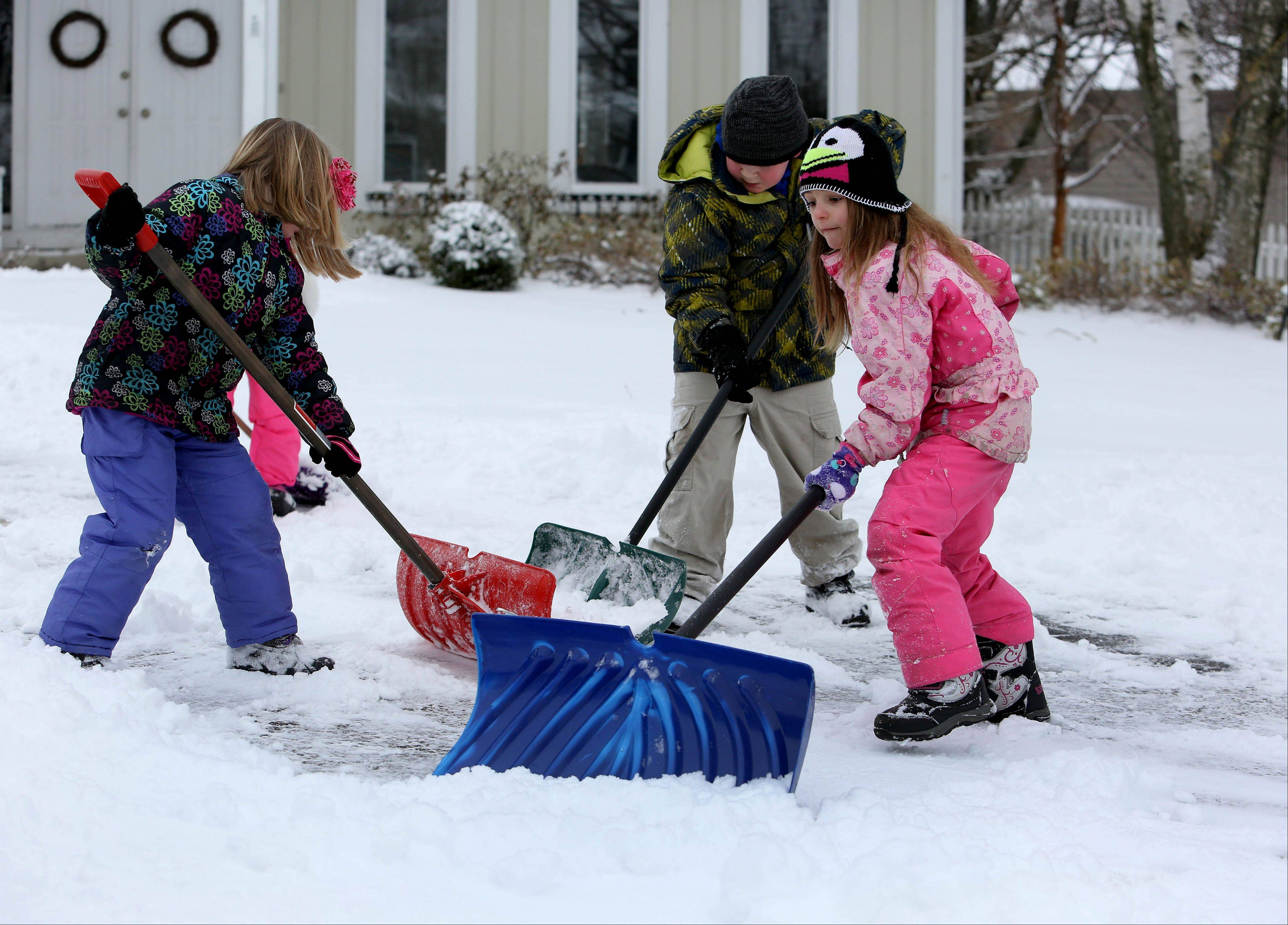 Colette Knierin, 6, Cade Knierin, 9, and Lilly Berta, 6, work to clear the driveway before school Friday after an overnight storm dumped several inches of snow on Naperville.