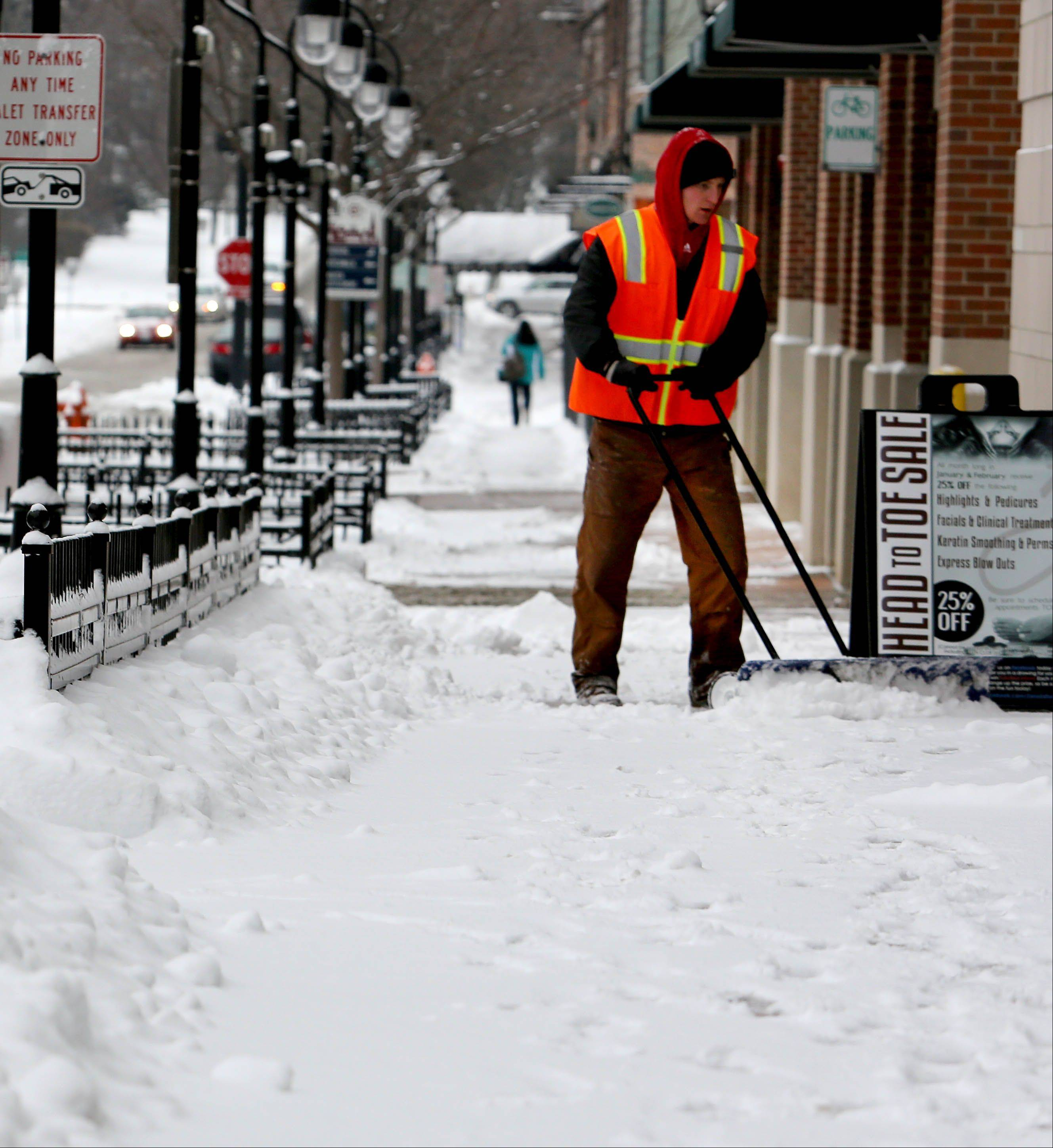 Tim Beckteo works to clear the sidewalks Friday in downtown Naperville after an overnight snow.