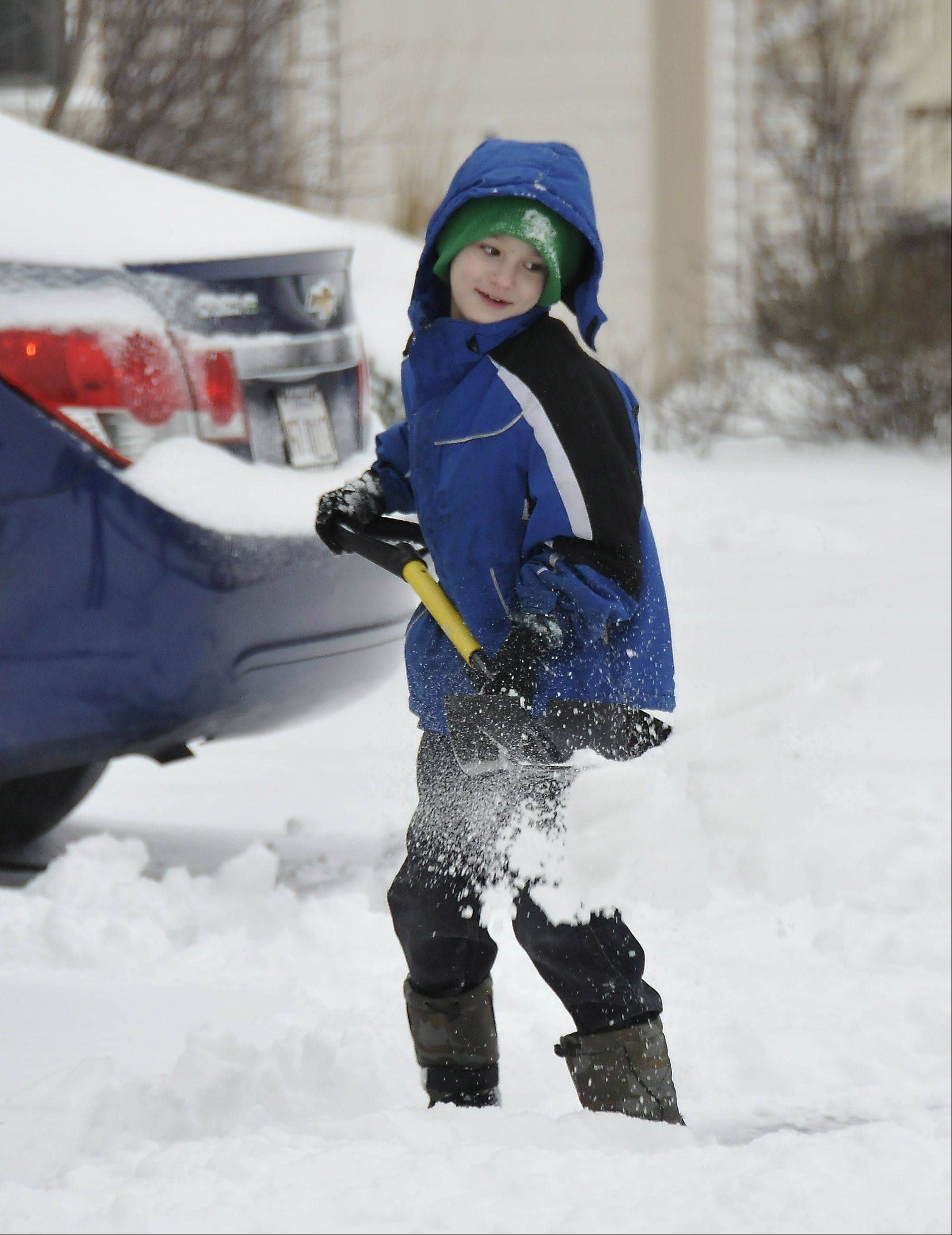 Alec Enright helps his mom, Kelly, shovel snow Friday outside their Itasca home.