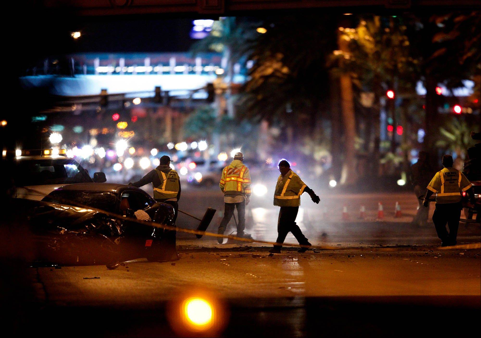 Tow truck drivers clean up and tow away cars involved in a drive-by shooting on Las Vegas Boulevard in Las Vegas Thursday, Feb. 21, 2013.