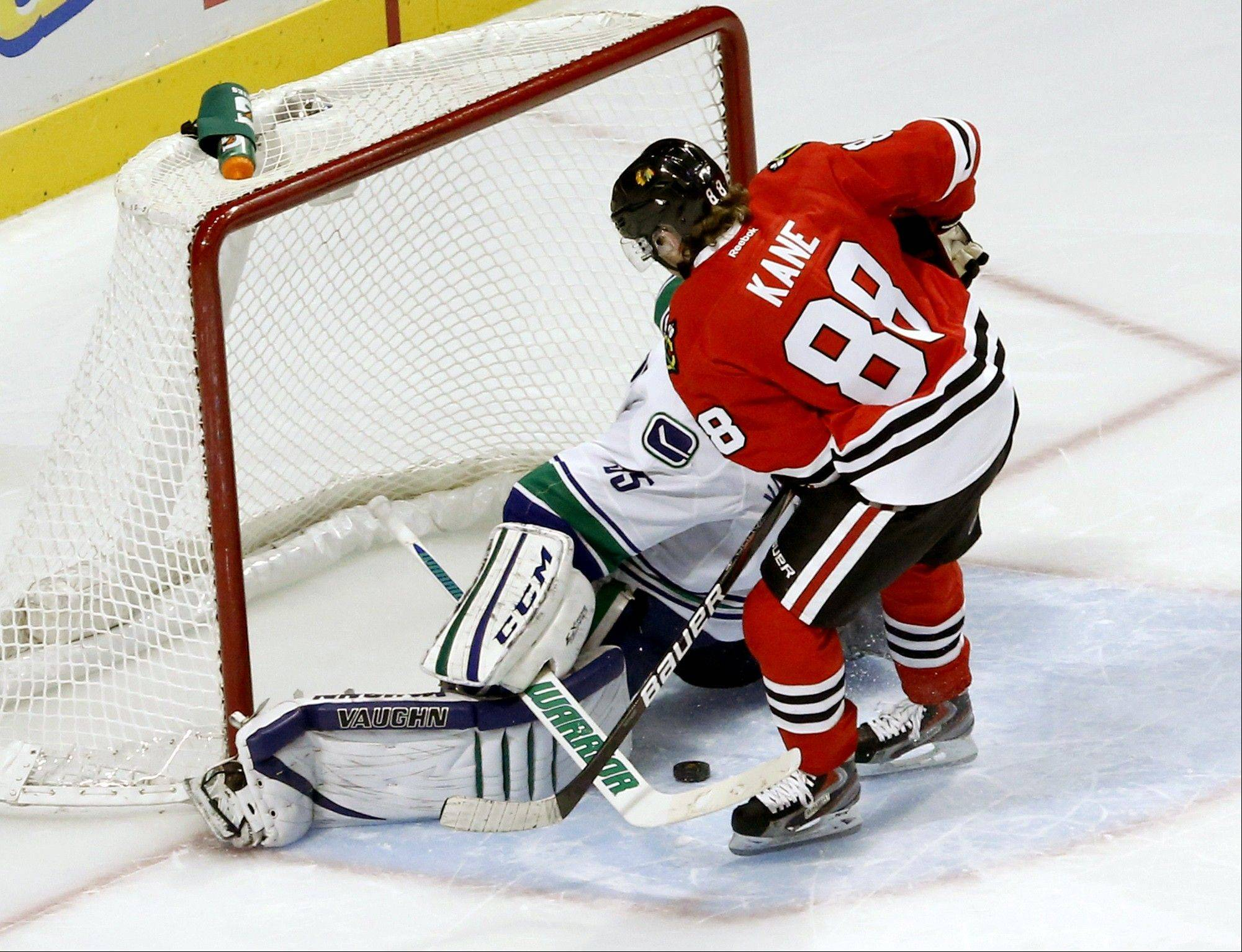 Chicago Blackhawks right wing Patrick Kane (88) scores between the legs of Vancouver Canucks goalie Cory Schneider during a shootout Tuesday in Chicago. Now that the Hawks have a shot at the best season start ever, they're thinking, might as well do it.
