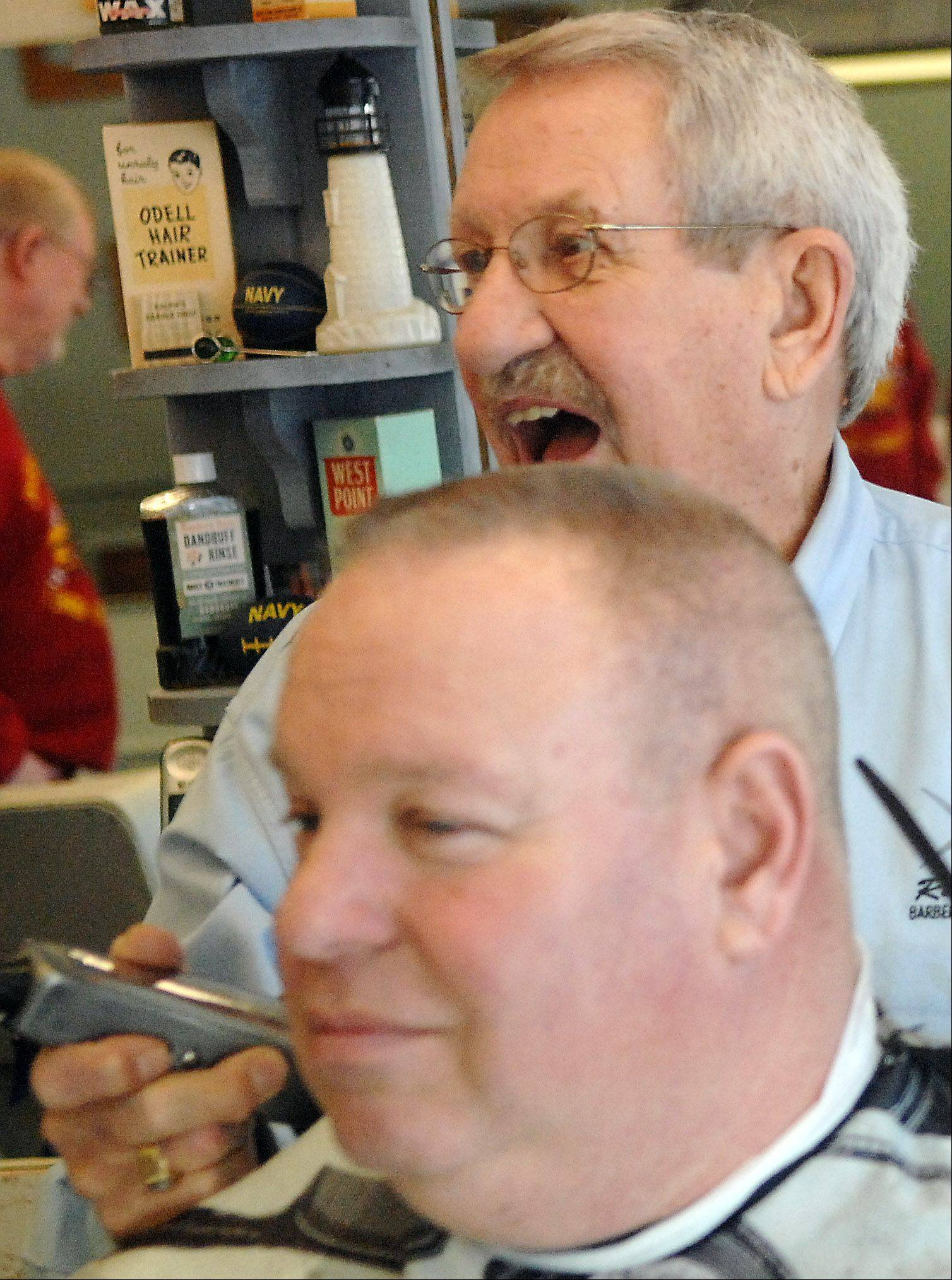 Ralph Ward jokes with another customer while working on Don Meyer of South Elgin this week at Ralph's Barber Shop in Elgin. Ward, who turns 80 today, is likely the longest practicing barber in Elgin.