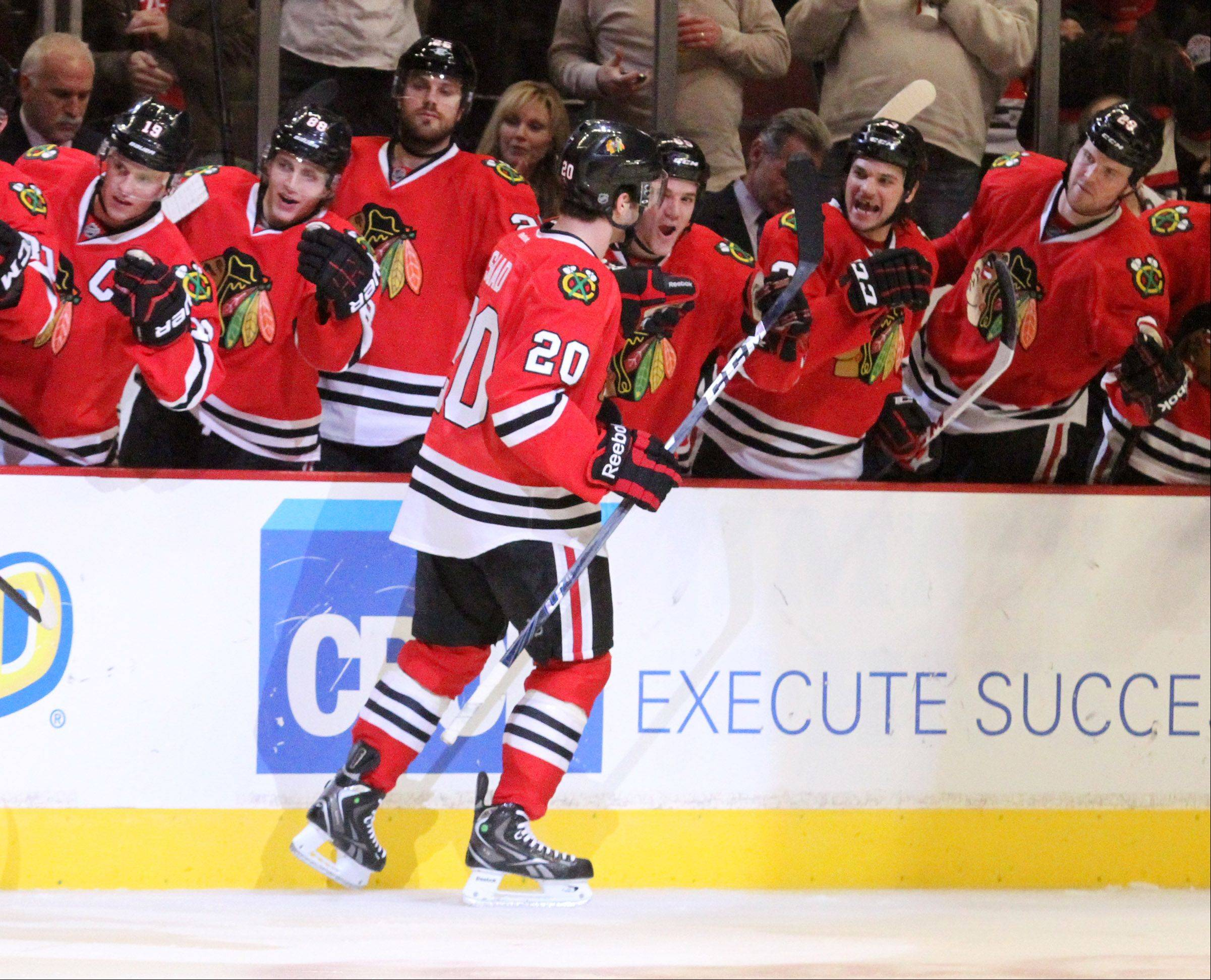 The bench gives Chicago Blackhawks left wing Brandon Saad a hand after Saad scored the second goal in the 3rd period as the Blackhawks win 2-1 against the San Jose Sharks at the United Center on Friday.