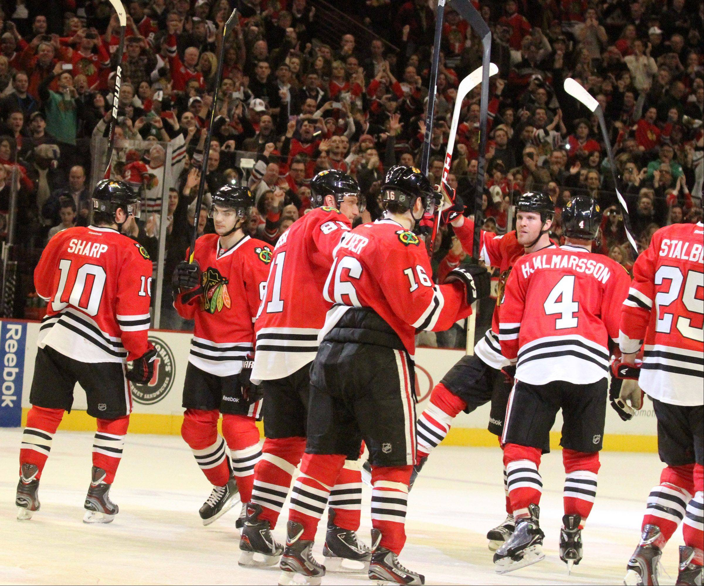 The Blackhawks raise their sticks after winning 2-1 against the San Jose Sharks at the United Center on Friday.