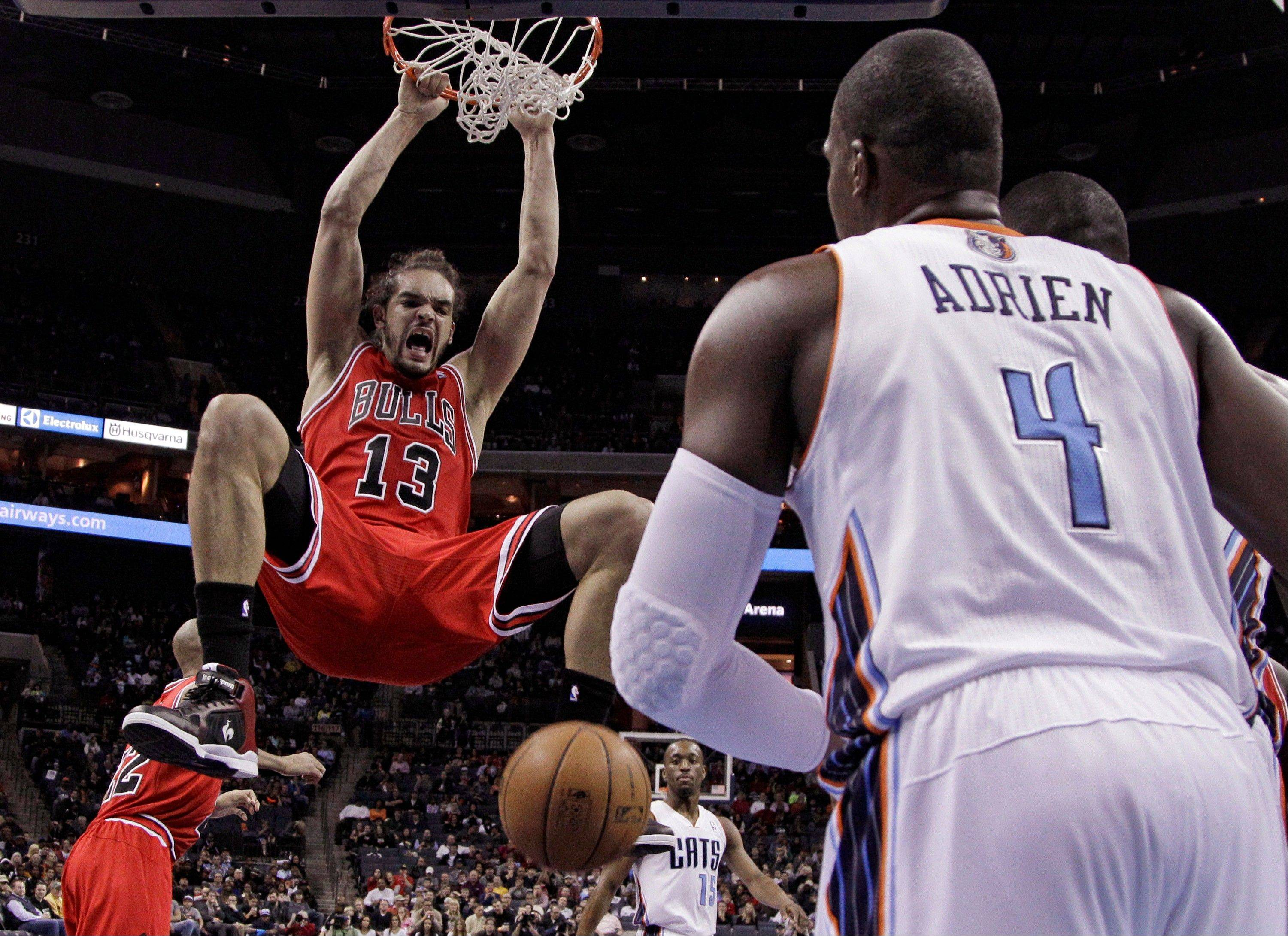 Bulls' Joakim Noah (13) dunks as Charlotte Bobcats' Jeff Adrien (4) looks on during the first half of an NBA basketball game in Charlotte, N.C., Friday, Feb. 22, 2013.