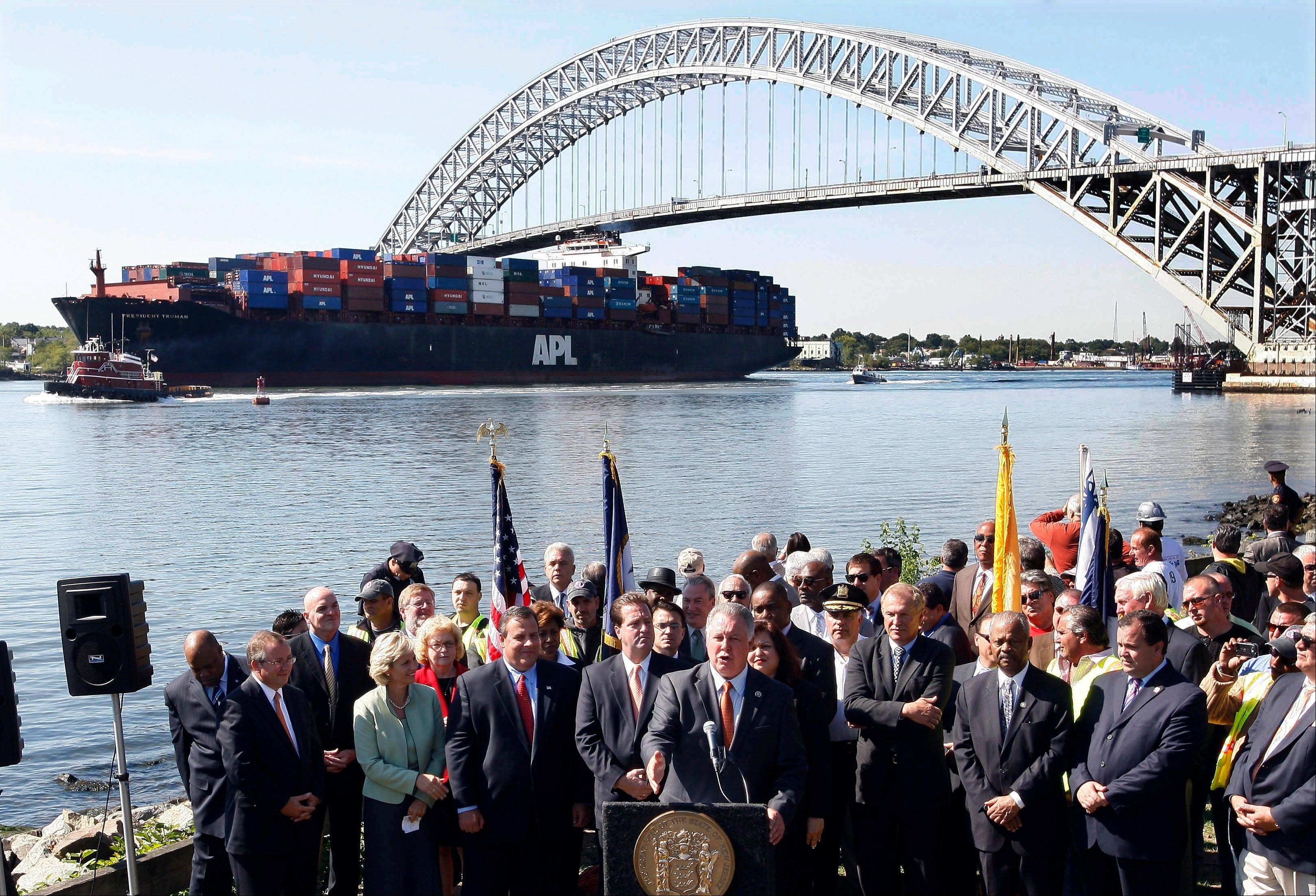Associated Press/Sept. 21, 2010 The President Truman, a large cargo ship, passes under the Bayonne Bridge in Bayonne, N.J., as New Jersey Gov. Chris Christie, third left, front, and Lt. Gov. Kim Guadagno, fourth left, front, listen with others, as Rep. Albio Sires of New Jersey talks about plans to raise the height of the bridge to accommodate the larger next generation of cargo ships.