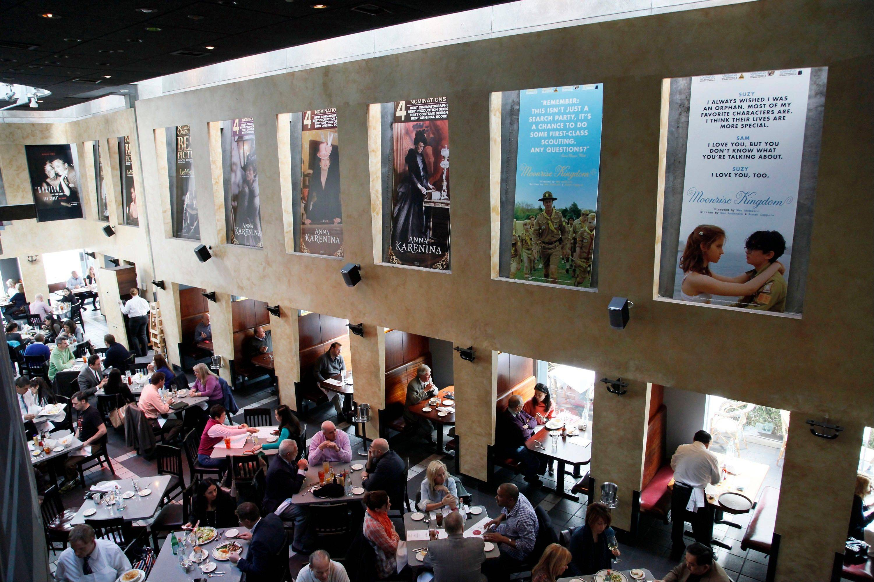 People have lunch Thursday beneath Oscar posters at Kate Mantilini restaurant in Beverly Hills, Calif. The 85th Academy Awards are Sunday.
